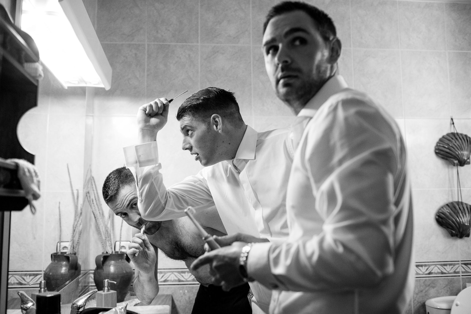 This is the best black and white getting ready photo of groom prep on a wedding day in Milagros in Spain. The groom, best man and usher all caught by surprise by Motiejus wedding photographer while second shooting for Adorlee