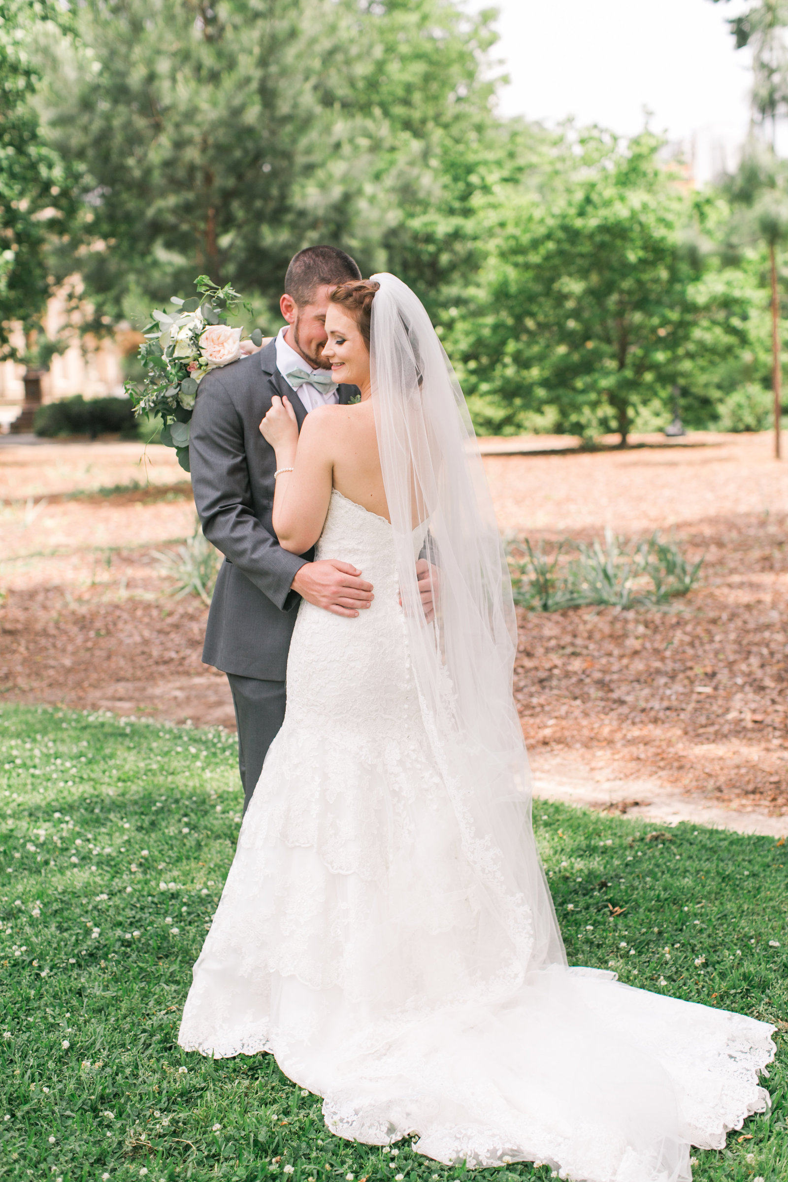 Groom holds bride above hips while she smiles and grabs his jacket