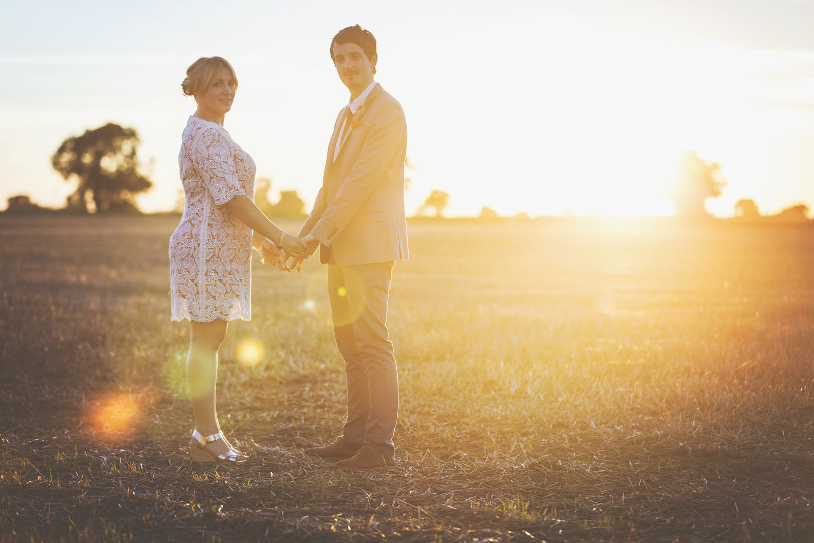 Wedding couple portrait in a field at sunset in Norfolk