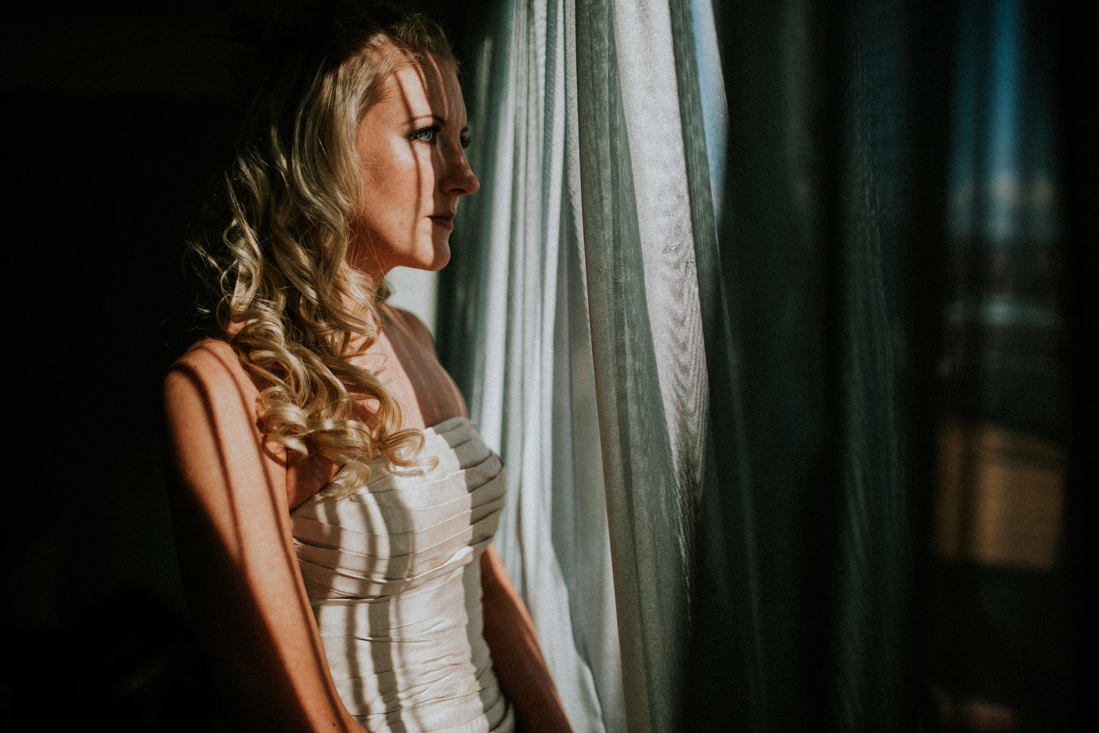 Bride stood looking out of window - Lancaster Wedding Photographer Jono Symonds