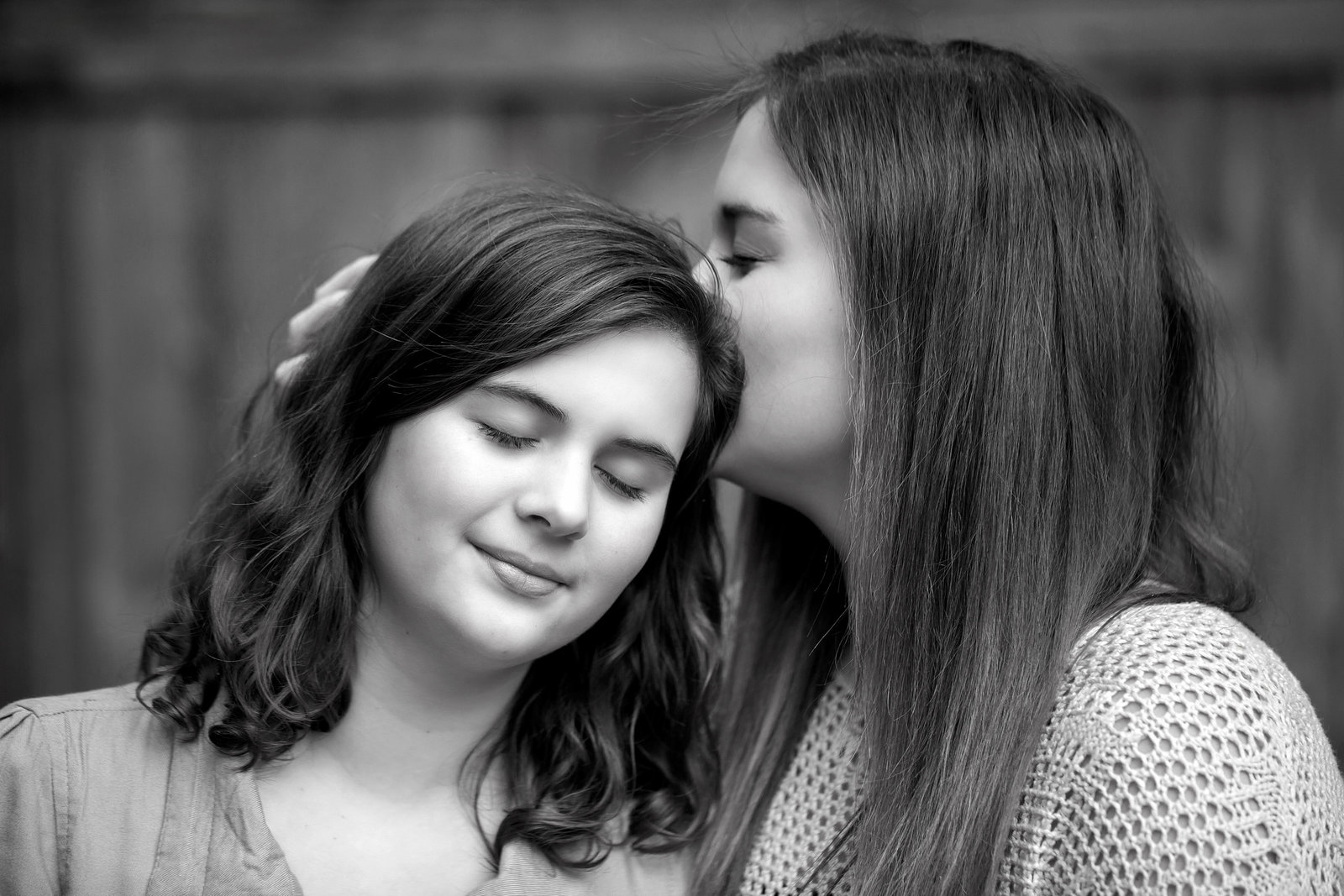 Sisters and best friends having a tender moment during outdoor photo session