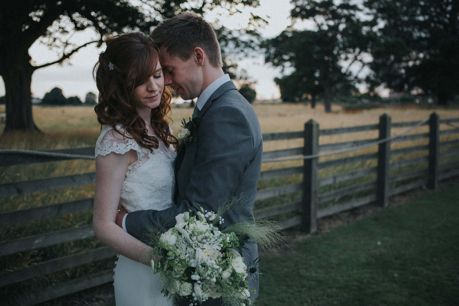 Bride & Groom hugging stood in front of a wooden fence by Yorkshire Wedding Photographer Jono Symonds