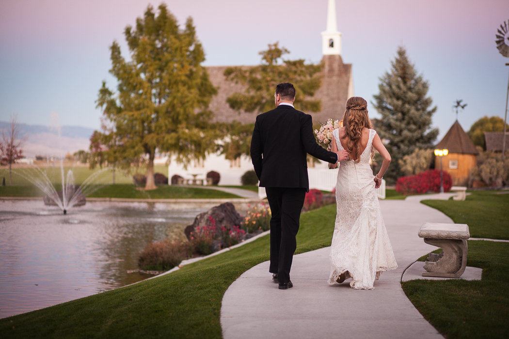 Fashionable newlyweds walk down a path towards their reception at Stillwater Hollow in Nampa, Idaho.