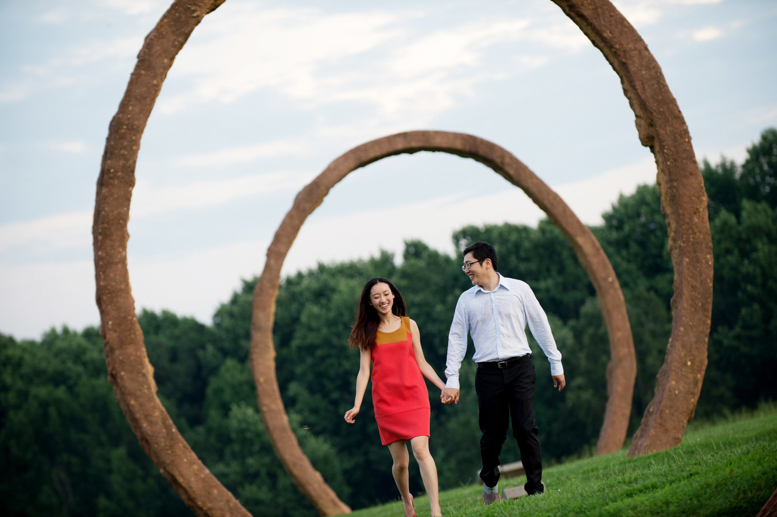 a couple run through the sculptures at nc museum of art