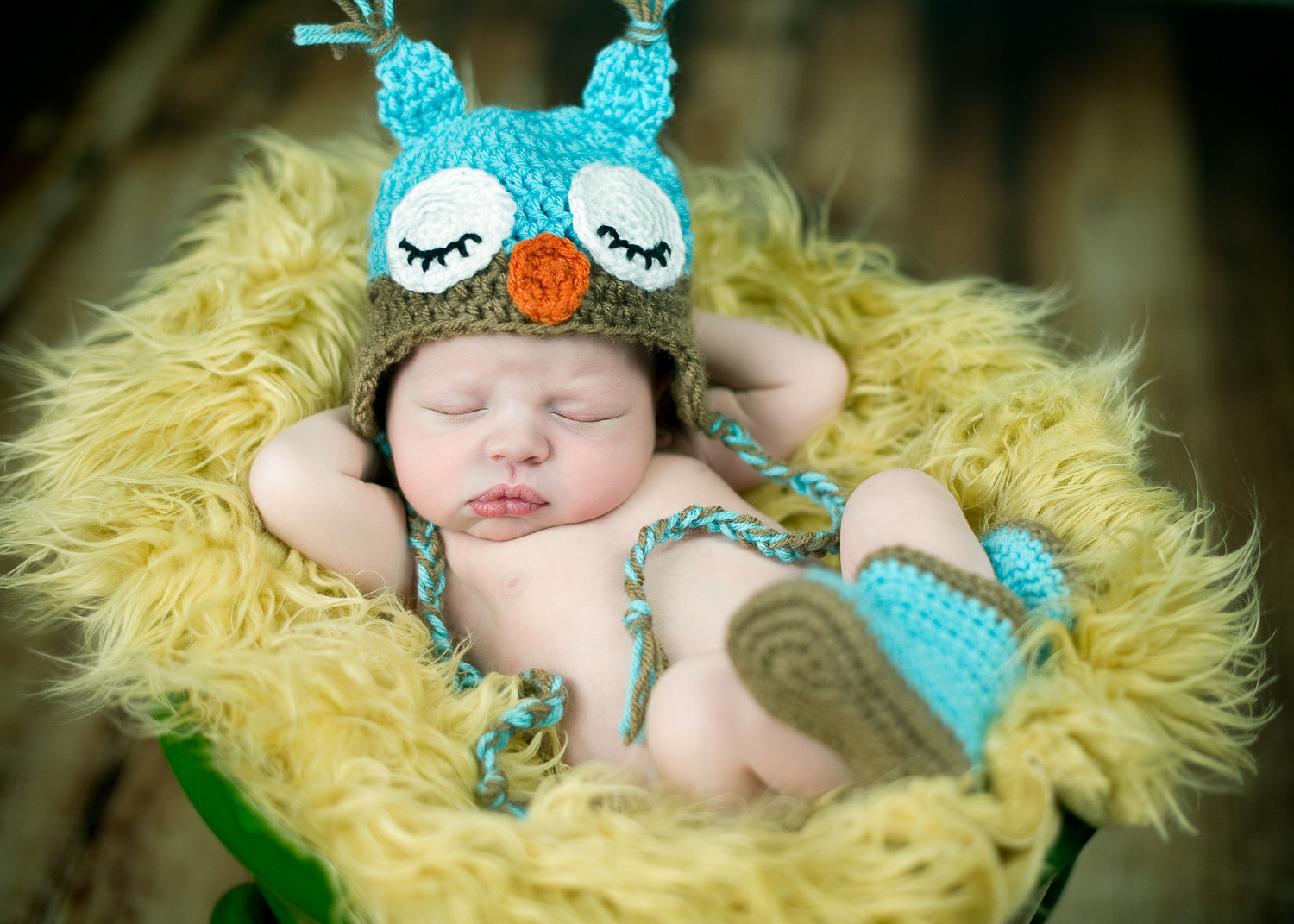 newborn baby sleeping in yellow flokati with crochet owl at and booties by homeschoolma