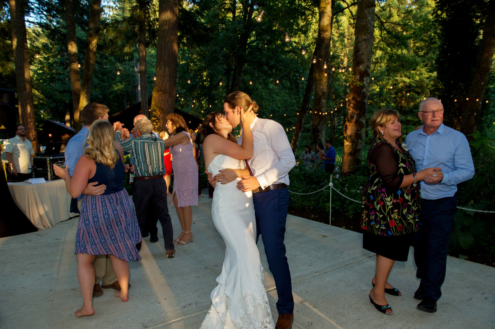 groom dips and kisses the bride on the dance floor at the reception