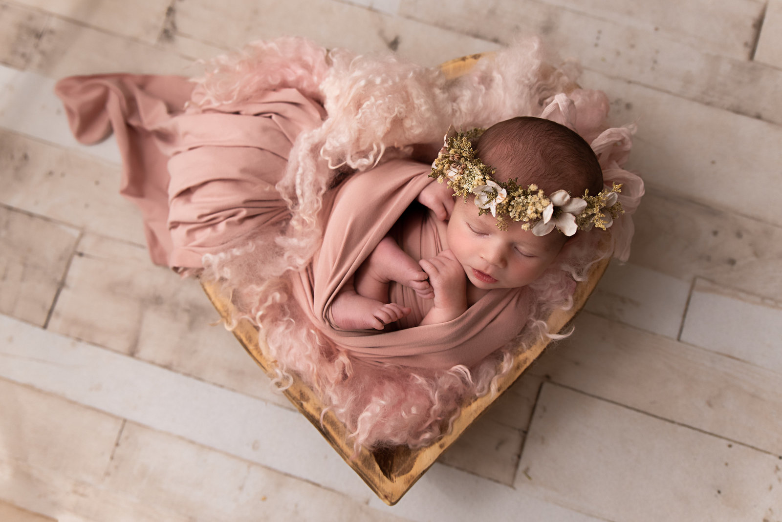 Newborn baby girl wrapped in pink fabric and asleep in a heart shaped bowl. She is lying in pink wool fluff and wearing a creamy colored floral crown