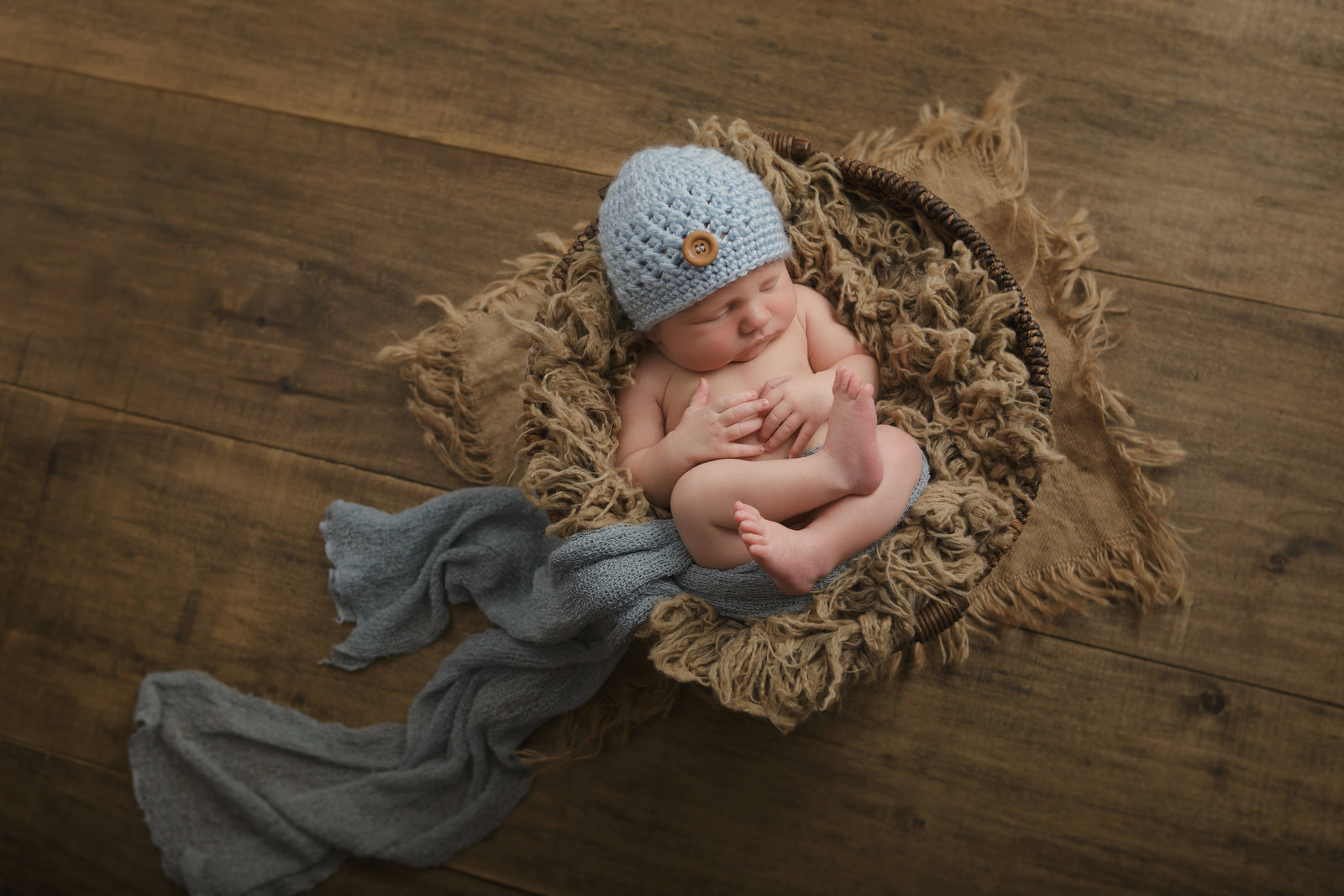 newborn baby boy curled up in a basket with fur and burlap on wood floor wearing a knit hat in the Hudson Valley NY by professional photographer Autumn Photography