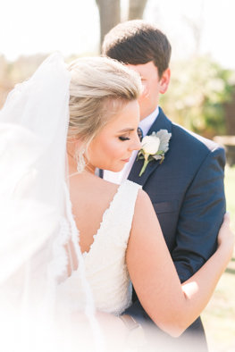 Groom whispers to bride as she looks over her shoulder