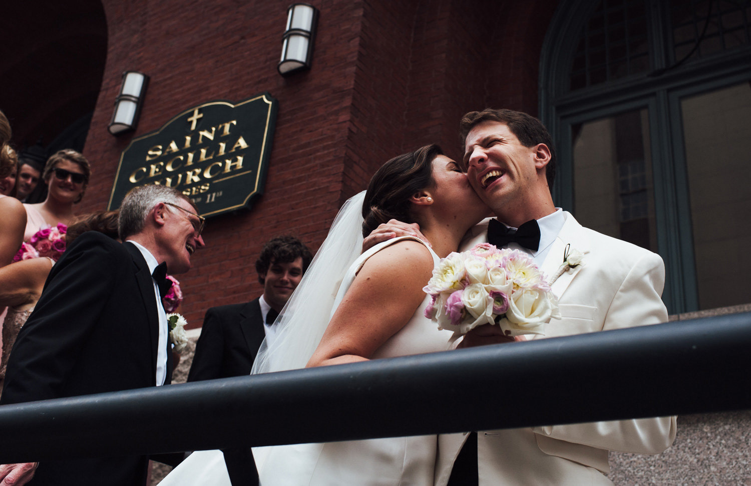 Bride kisses groom outside St. Cecilia Chruch, Boston, MA