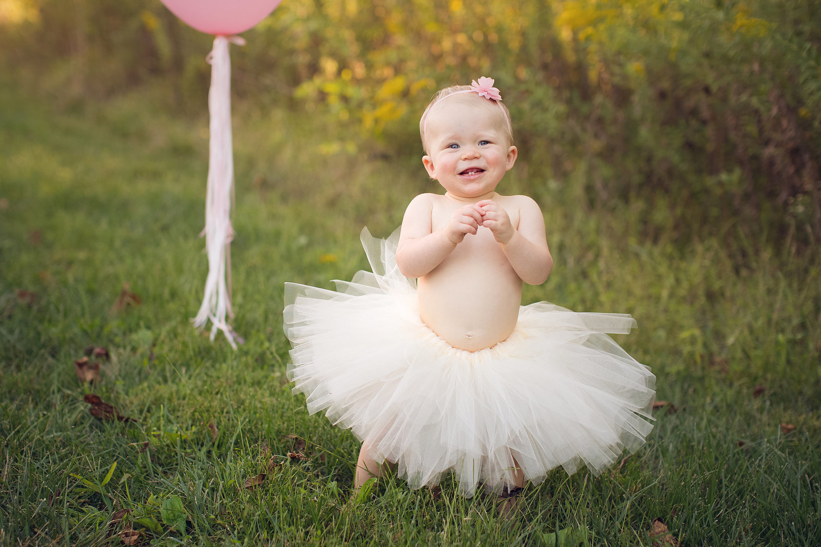 Smiling girl outside poses in pink tutu and smiling outside in grass