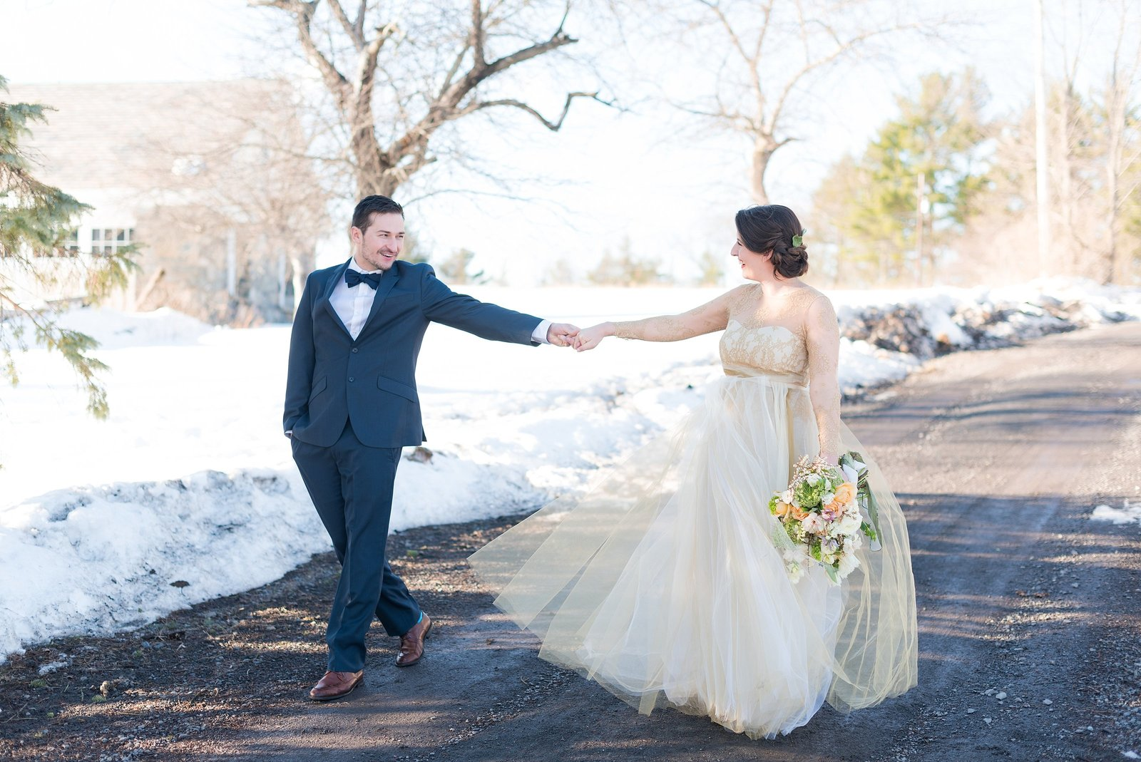Bride and Groom Playfully Walking in the Snow Photo