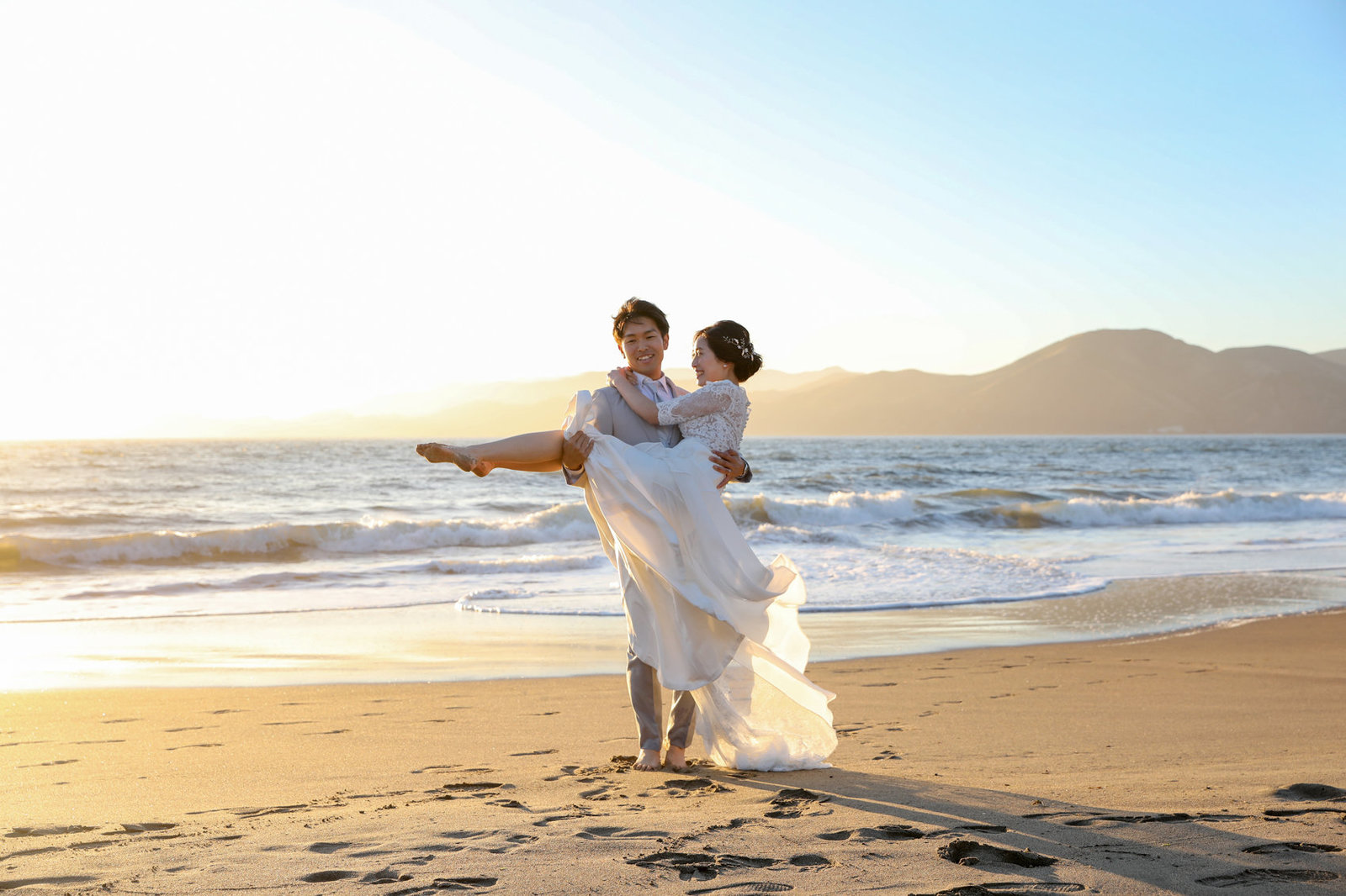 Couple lovingly poses in front of gorgeous sunset on the beaches of San Francisco