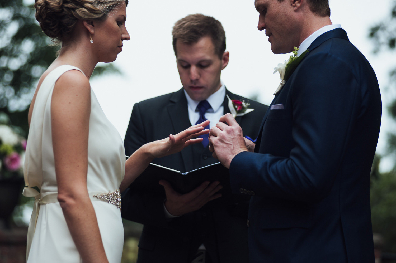 bride and groom exchange rings at outside ceremony