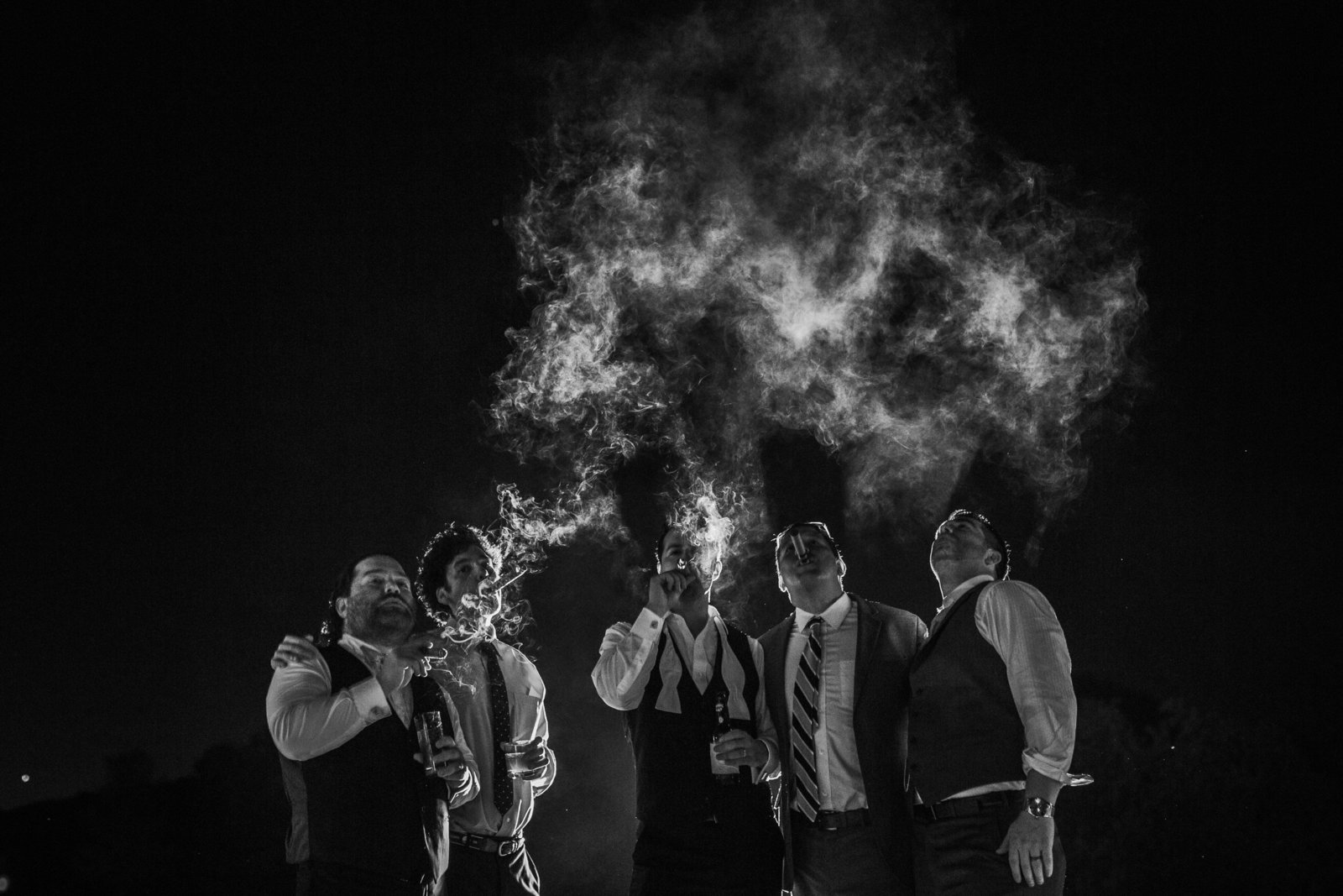 groomsmen enjoy cigars at night