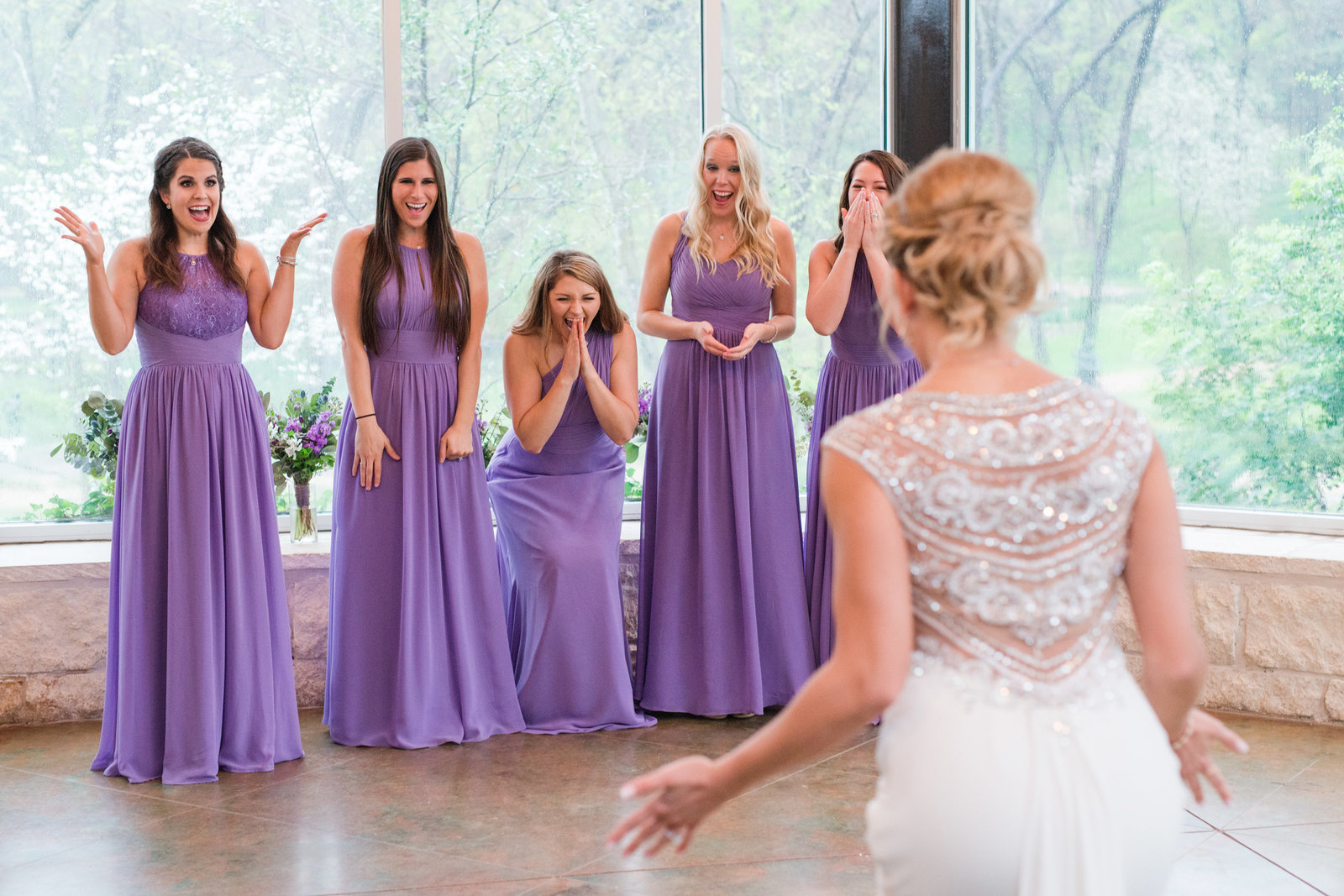 Bride reveals her dress to her bridesmaids in lavender at the Umlauf Sculpture Garden in Austin, Texas