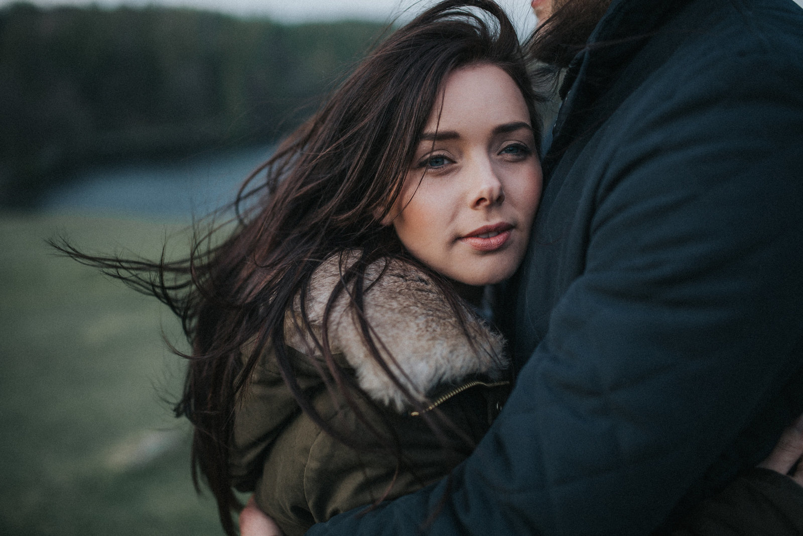 Girl hugging fiance with hair blowing in the wind