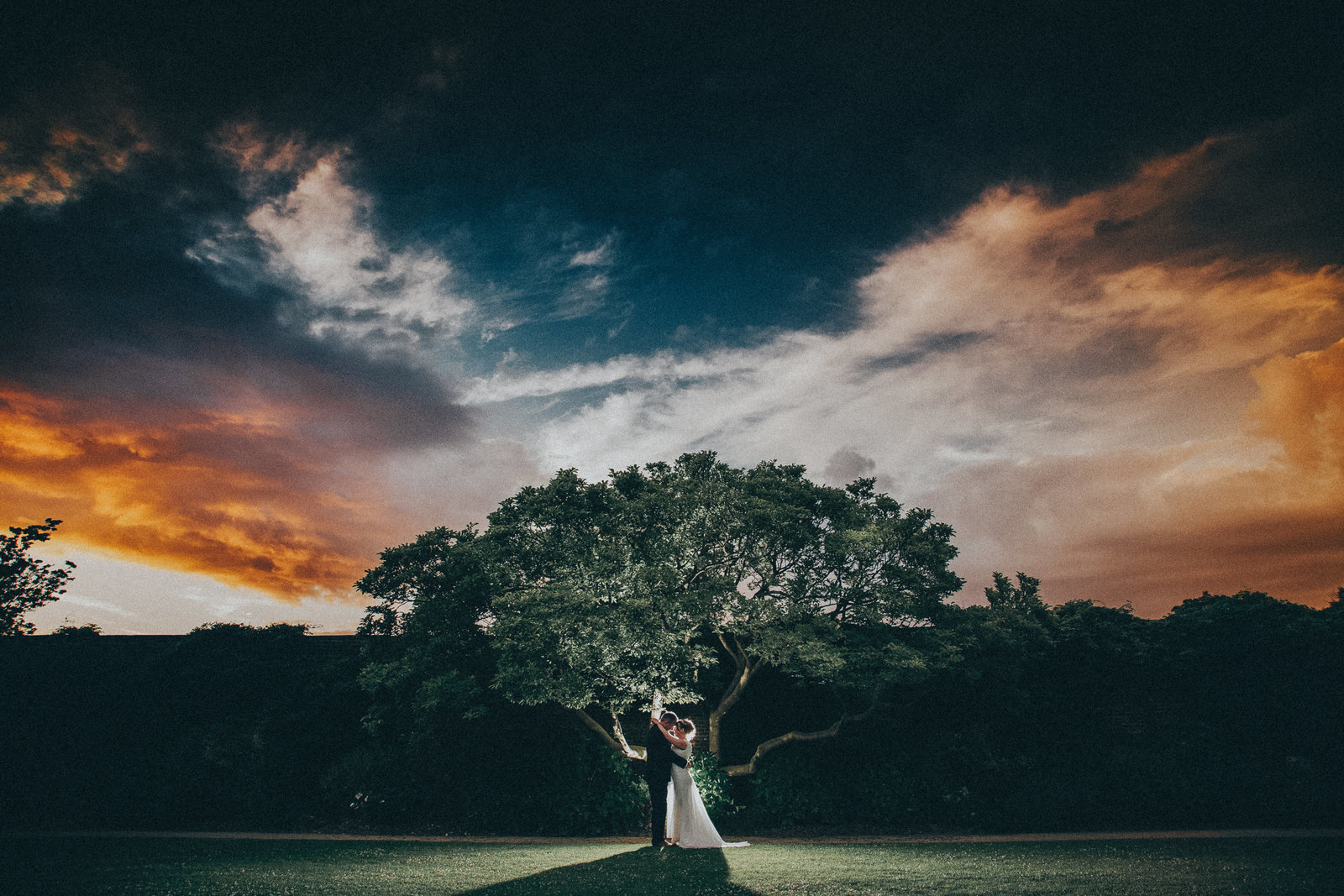 Couple stood under tree with dramatic clouds at sunset by Chorley Wedding Photographer Jono Symonds