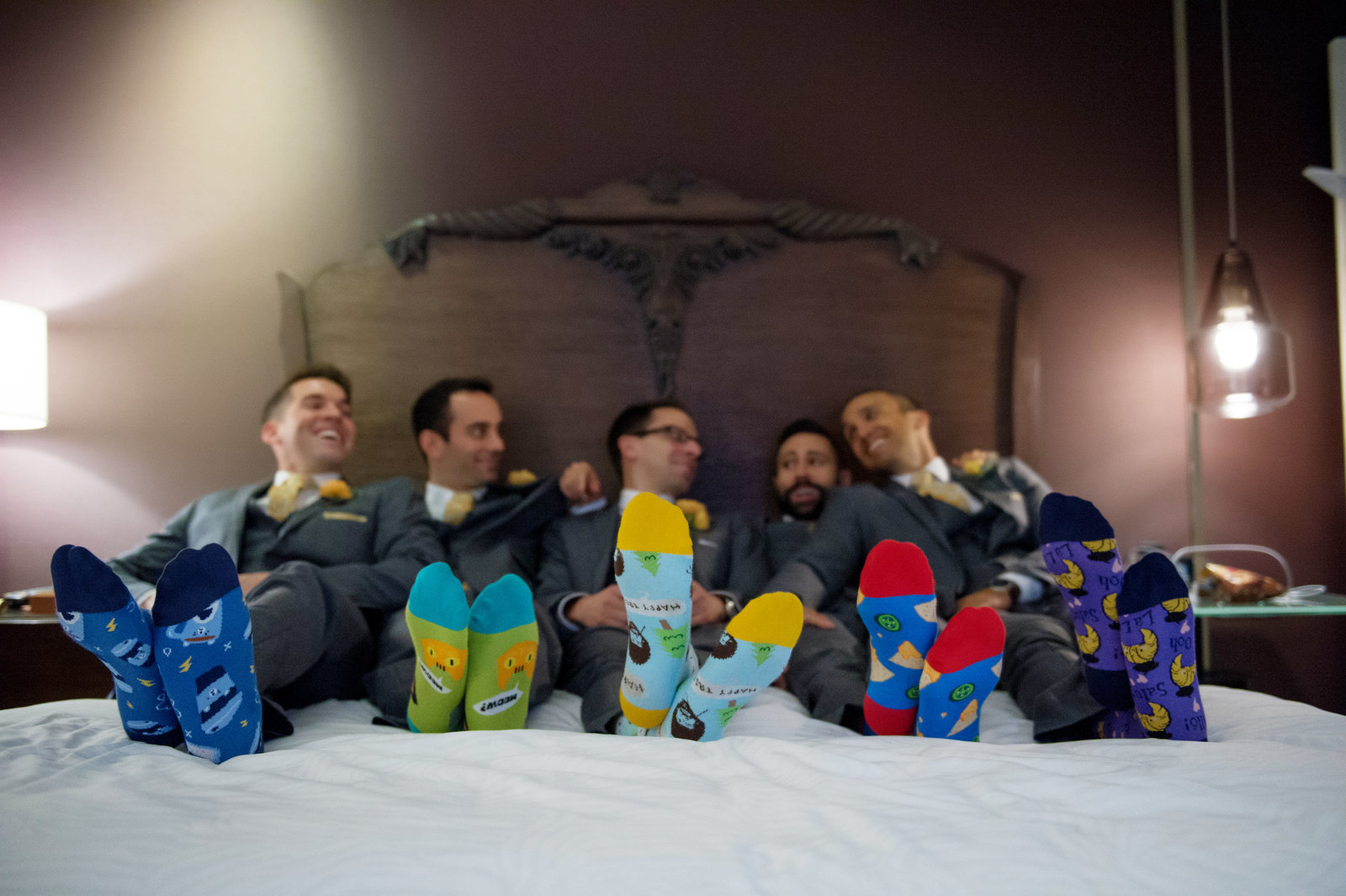 groomsmen lay on bed to show off their silly wedding day socks