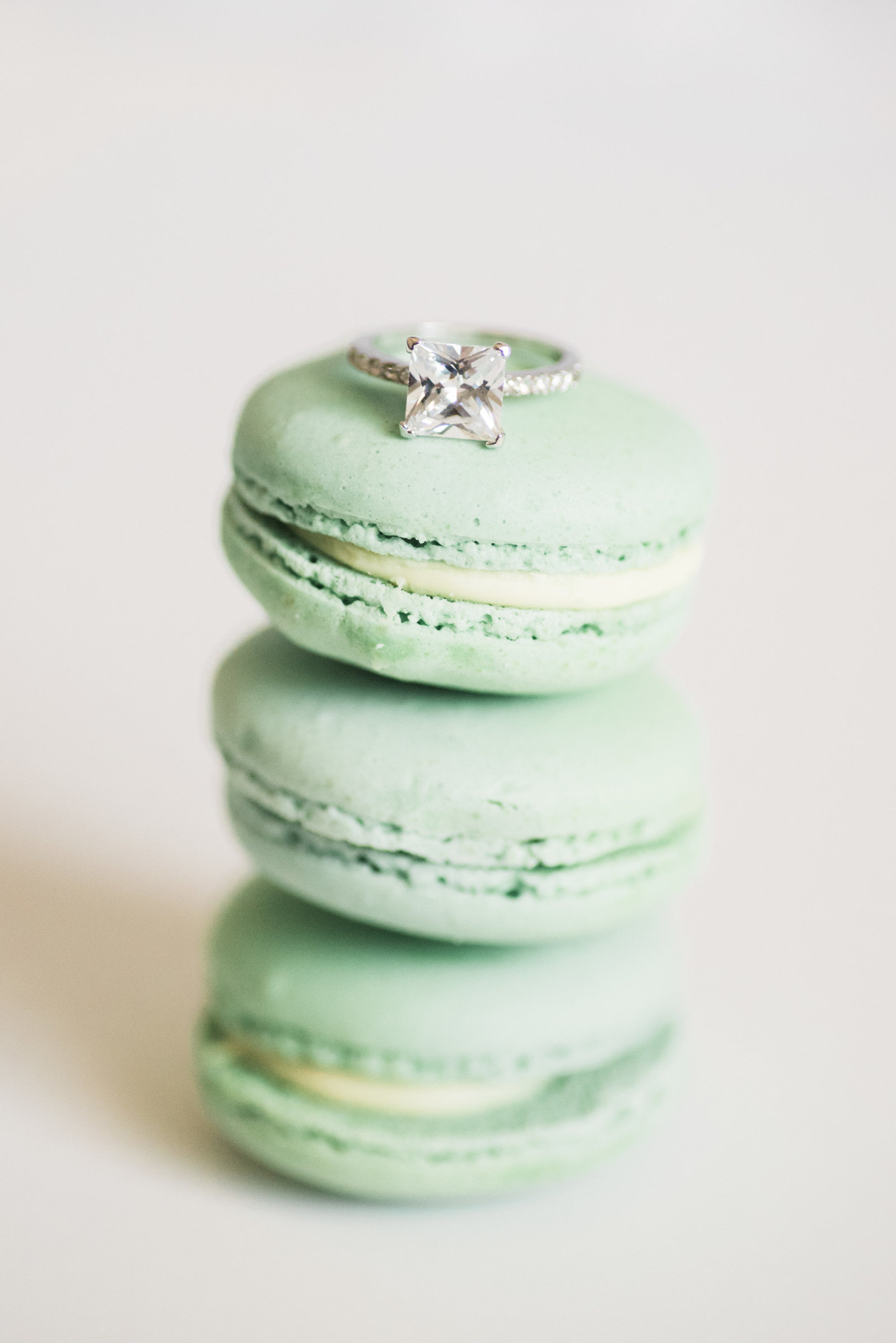 Green macarons and engagement wedding ring detail photo