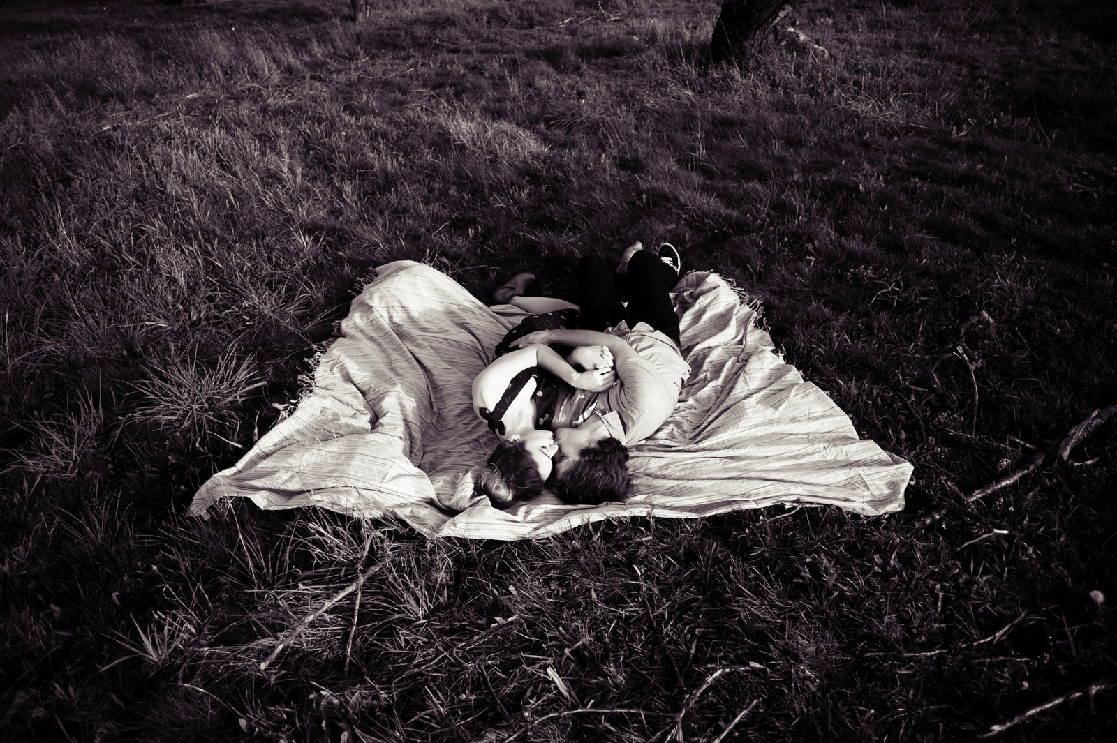 an engaged couple lay in the grass at an orchard in mt hood