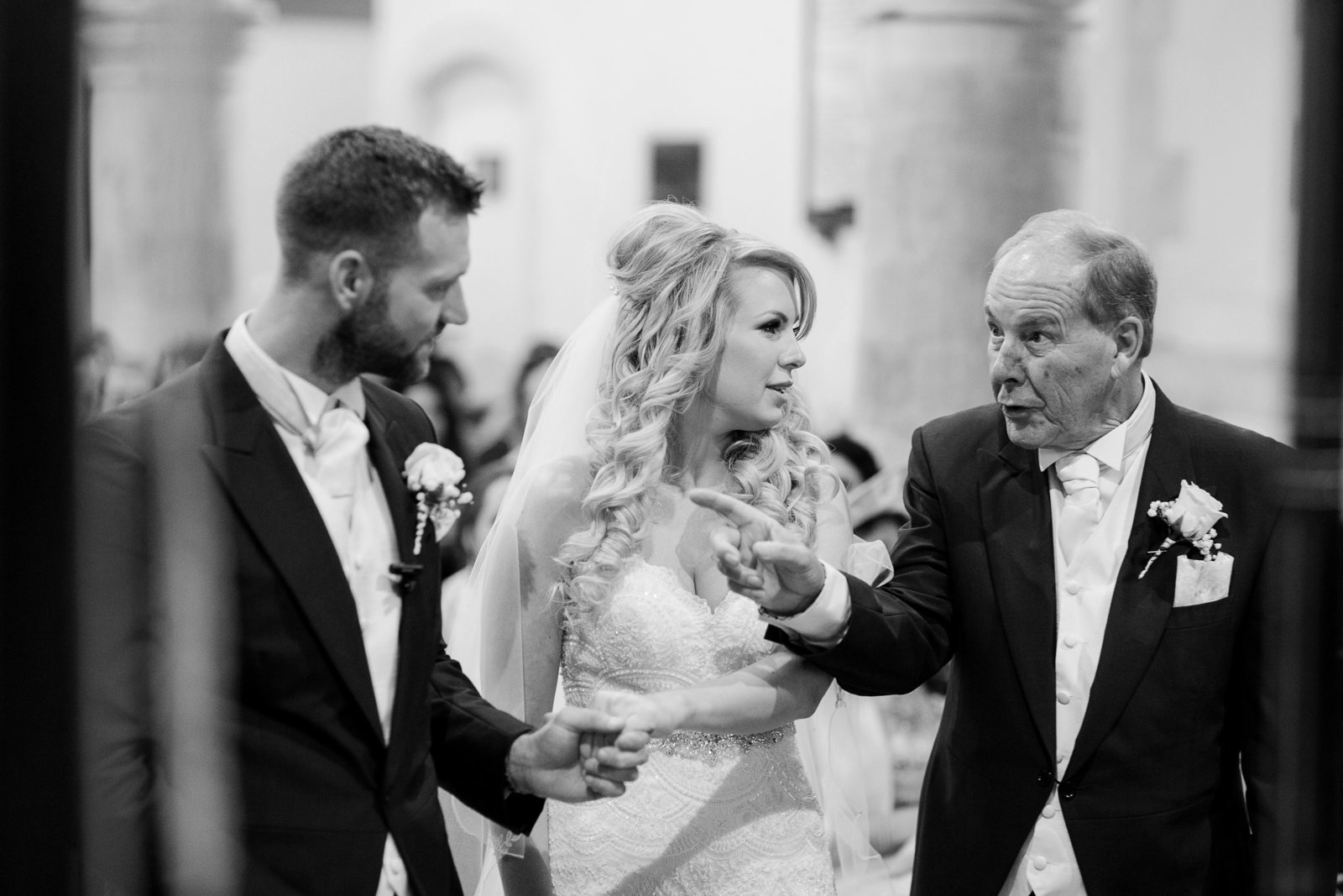 Amazing documentary wedding photography by Adorlee here, a black and white reportage photo in a church of the  father of the bride threatening the groom while giving his daughter away during their wedding ceremony in West Sussex