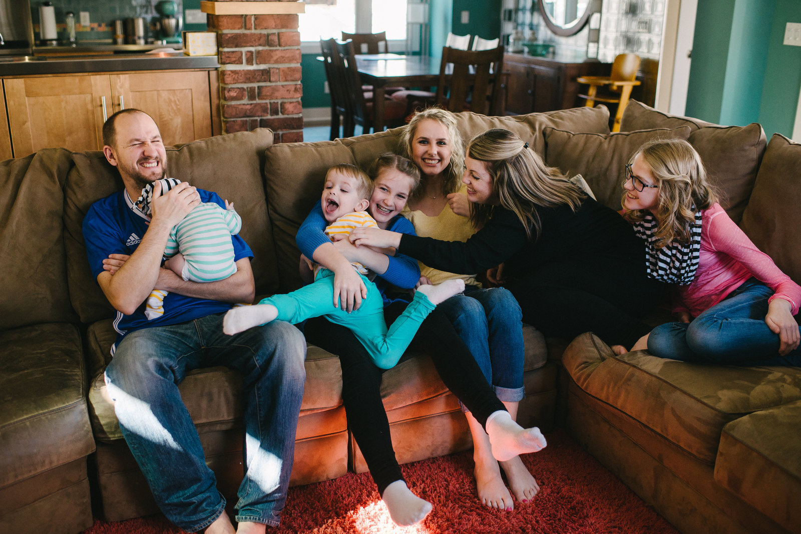 Boardman OH family piled on couch laughing