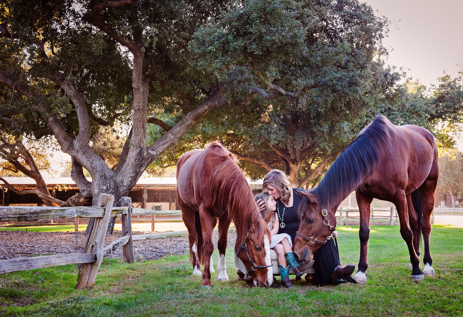 mom kissing daughter surrounded by horses by inGRACE photography