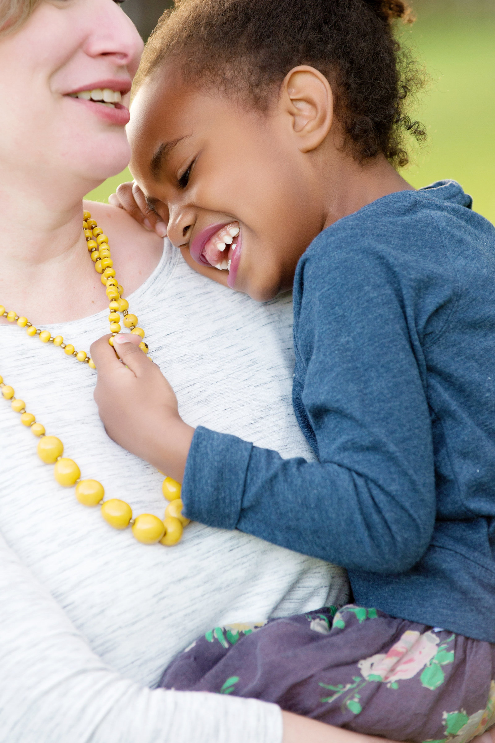 a mom holds her daughter as she laughs and plays with her yellow necklace