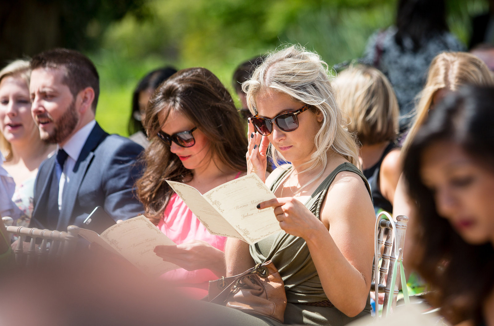 Lady guests captured by Adorlee Photography taking it all in reading  the order of service at this summer outdoor wedding ceremony at Castle Coombe