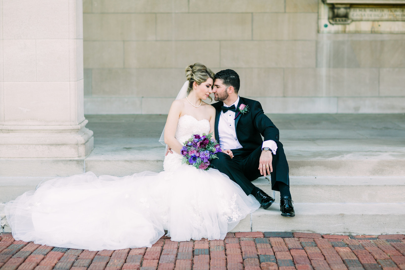 Bride and Groom, Zohra and Fahim, sit side by side on the steps of Washington University.