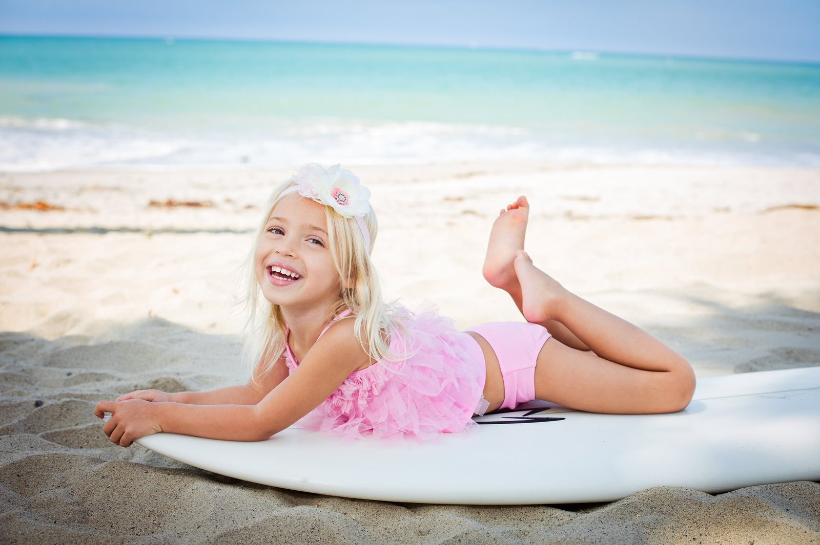 little girl playing on surfboard at beach