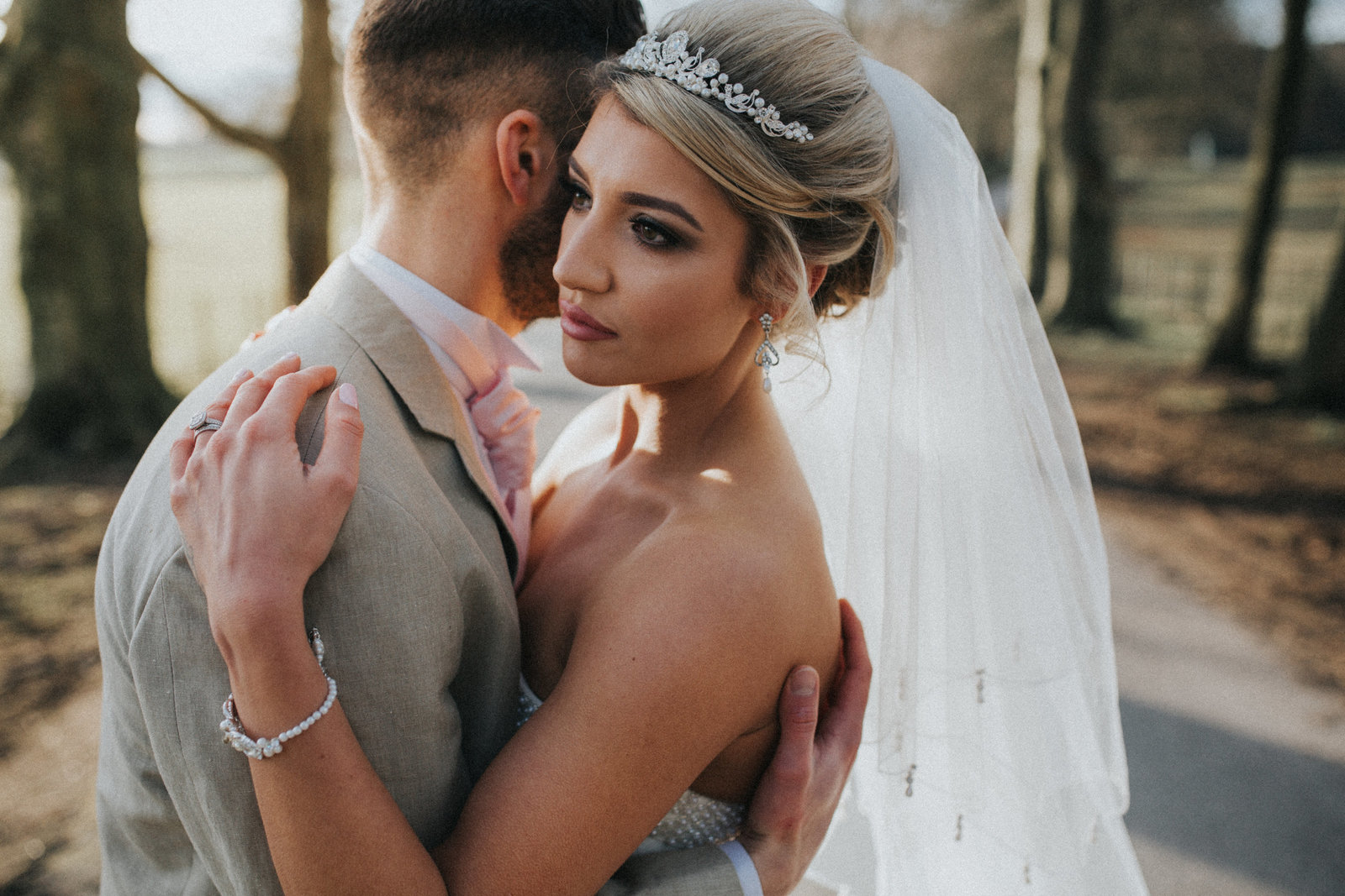 Couple hugging in the grounds of The Villa, Levens in Cumbria by Wedding Photographer Jono Symonds
