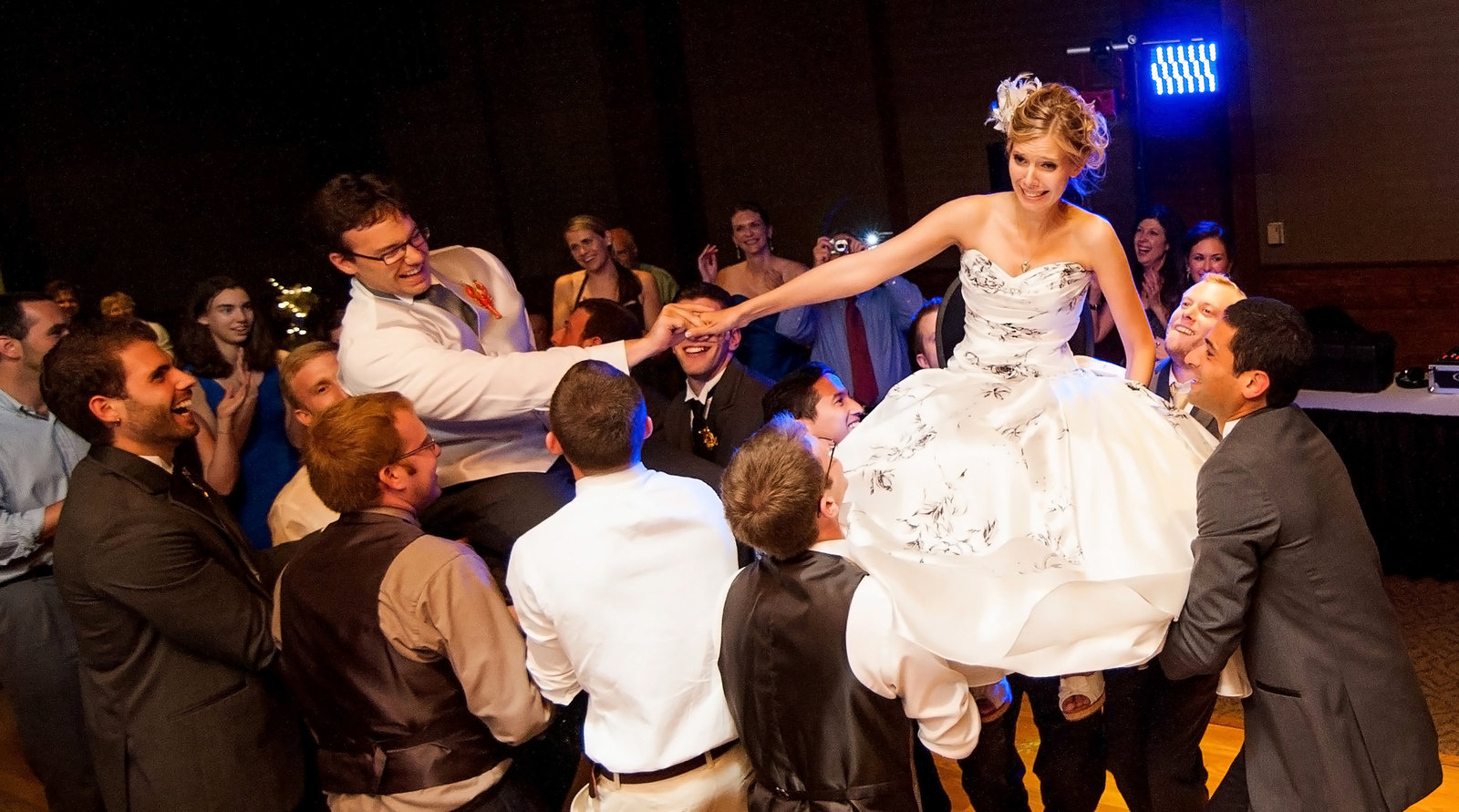 The bride holds onto her new husband during the Horah dance at Starved Rock Lodge near Utica, Illinois.