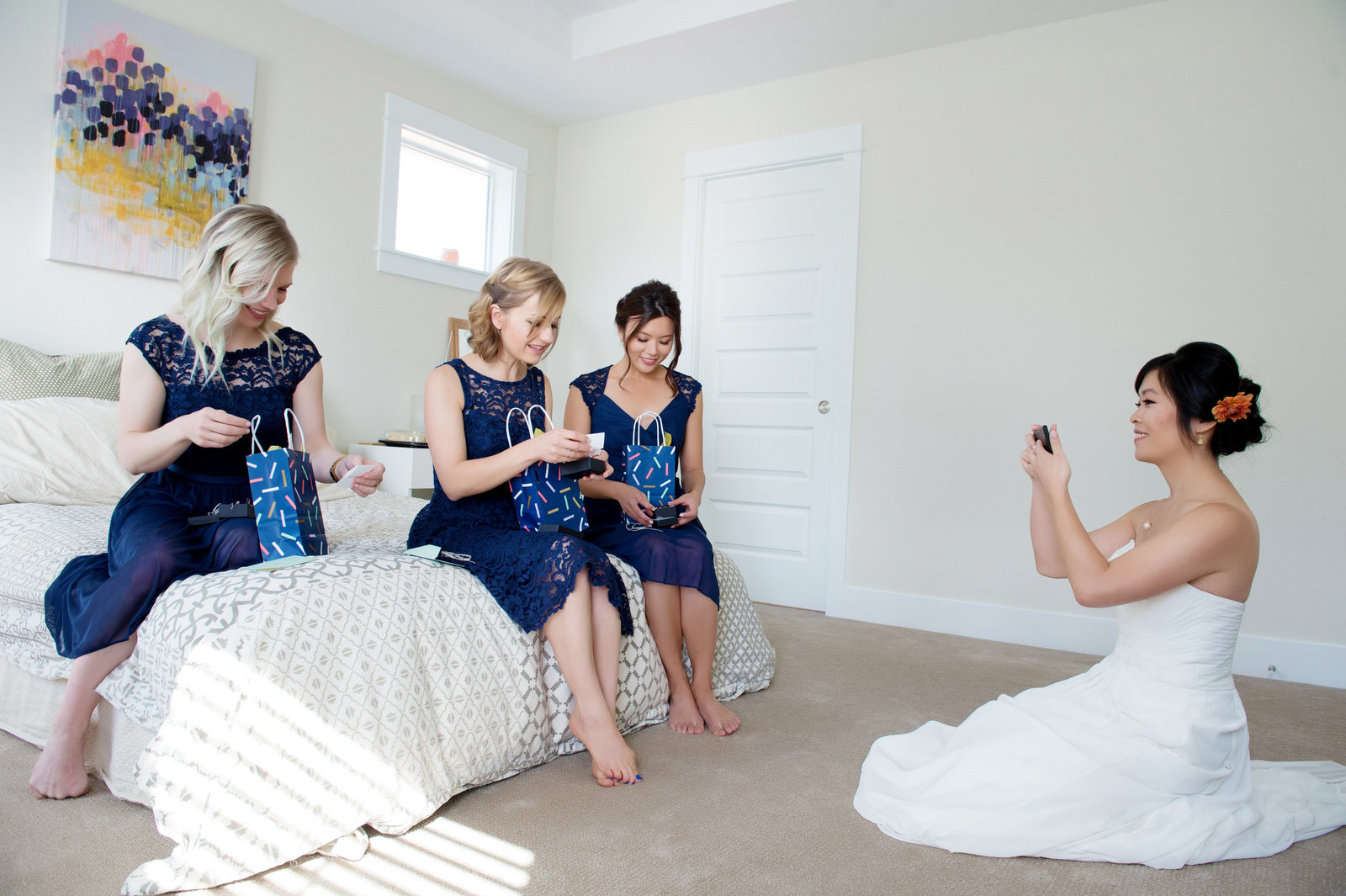 bride takes iphone photo of bridesmaids opening presents