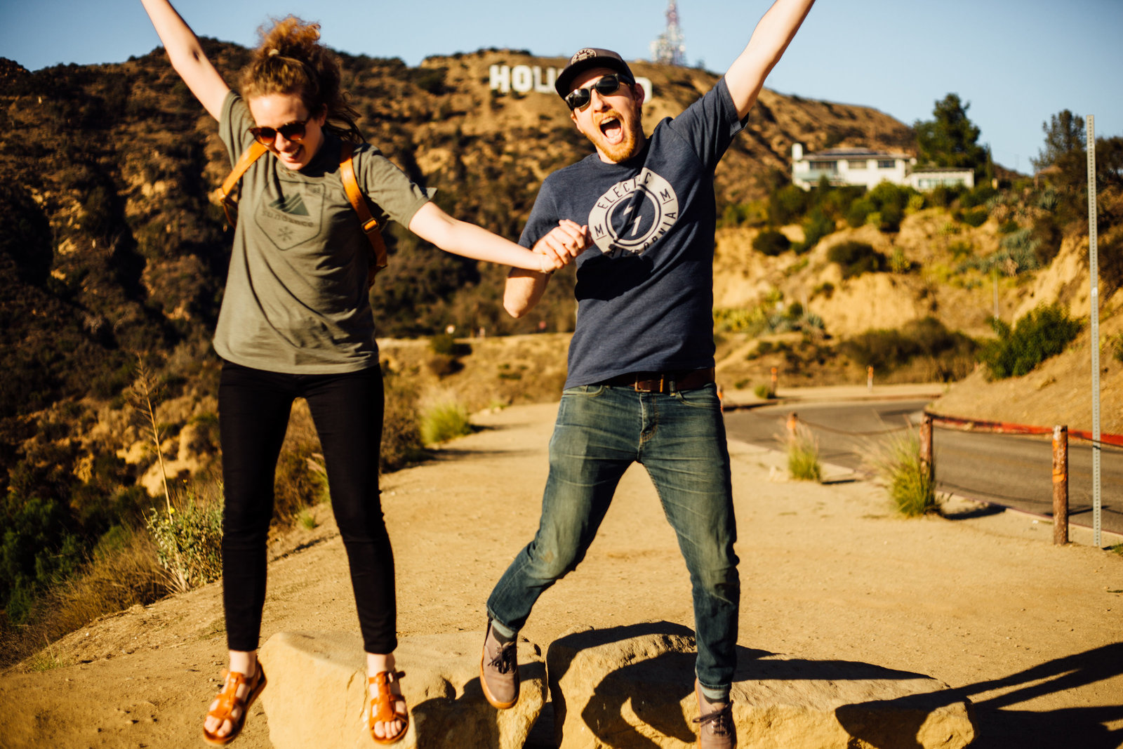 Couple jumping and smiling at Hollywood Sign in Los Angeles, California
