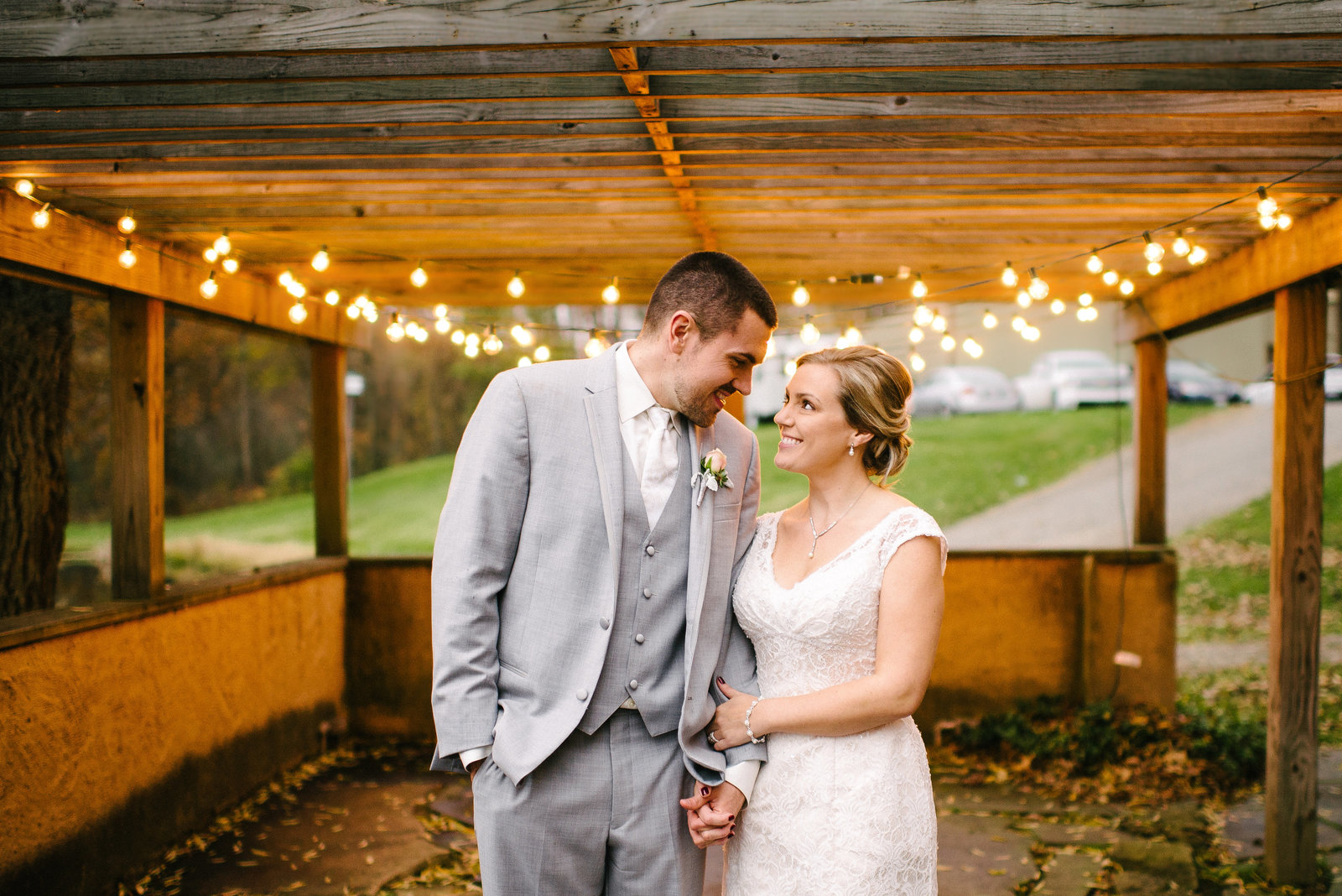 Snodes Restored Barn bride and groom standing underneath twinkle lights