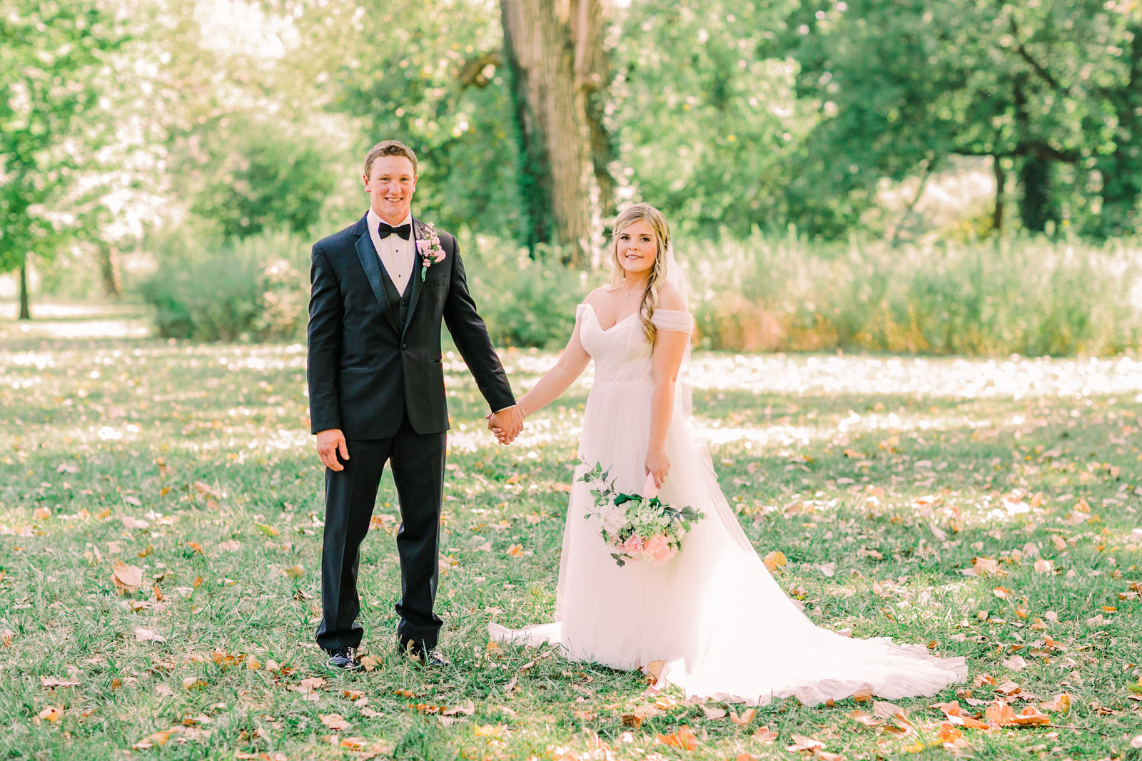 Bride and Groom, Katlyn and Levi, hold hands while standing side by side in a lush green area of Forest Park