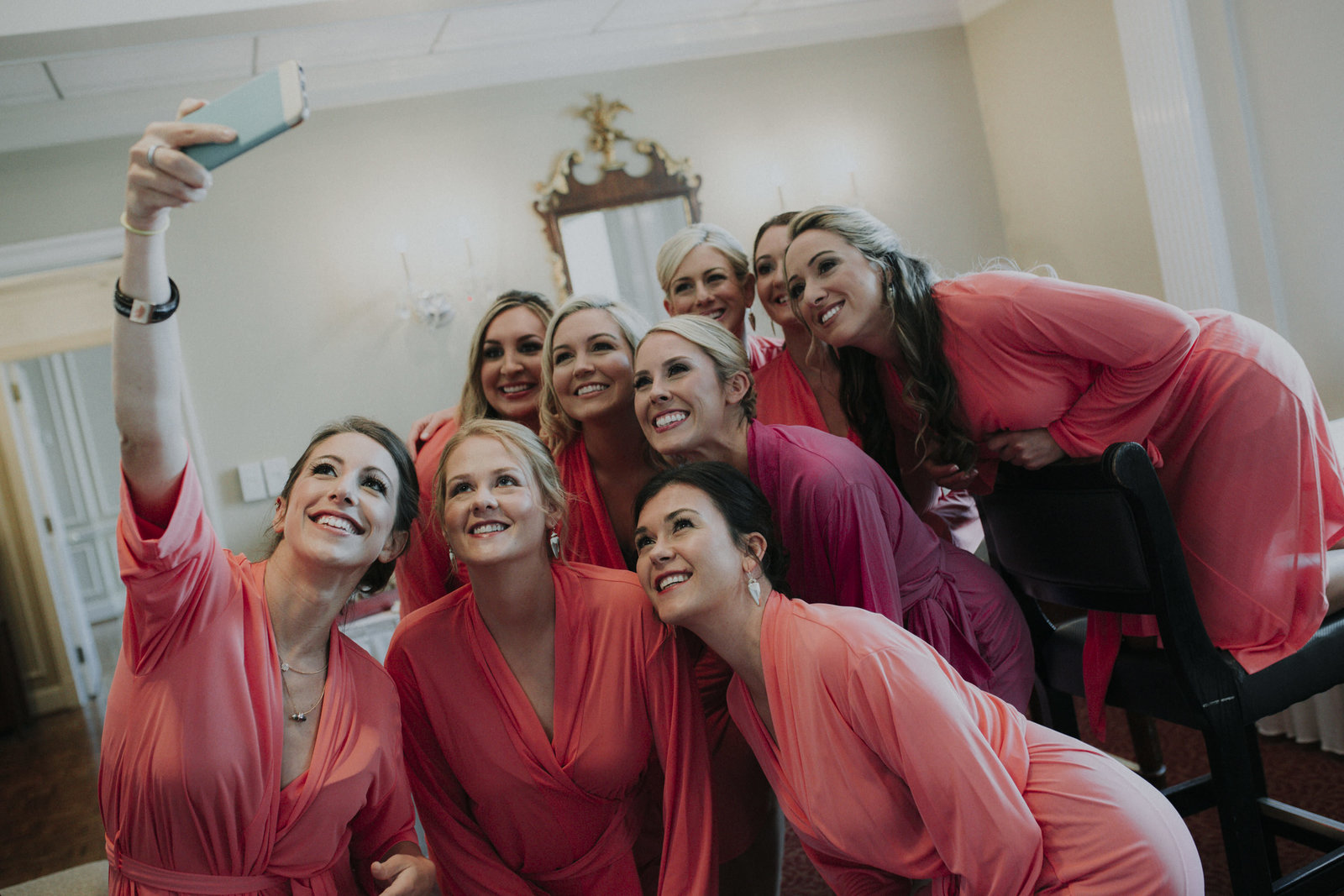 bridesmaids get ready for the wedding in pink robes