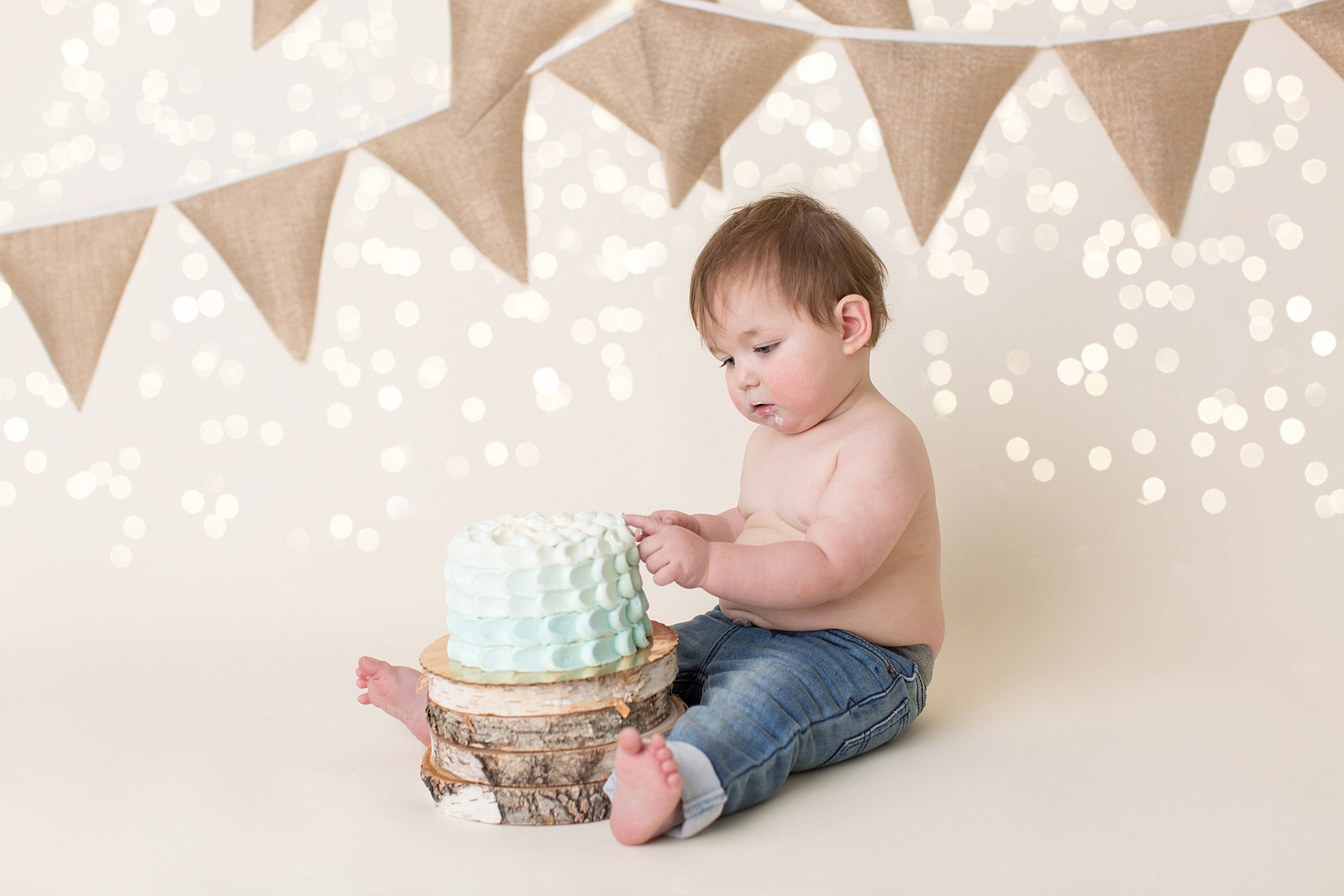 boy touches frosting on birthday cake