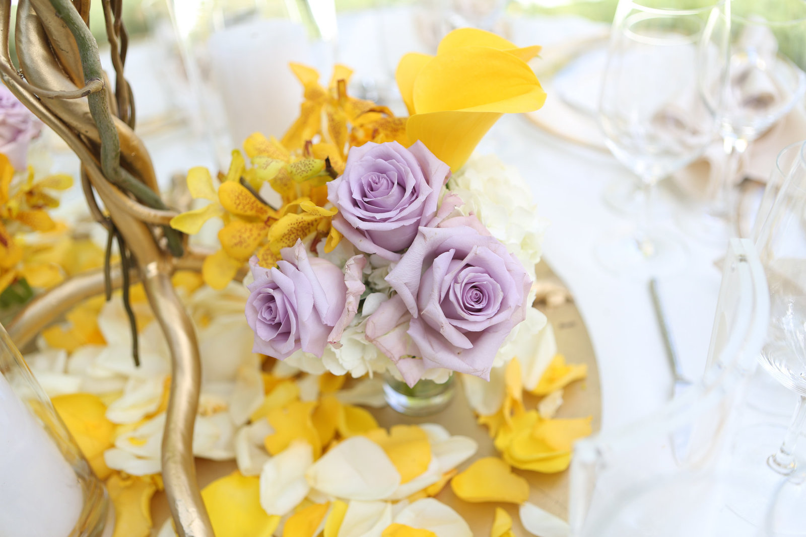 Stunning yellow and purple flowers decorate a table at a local wedding