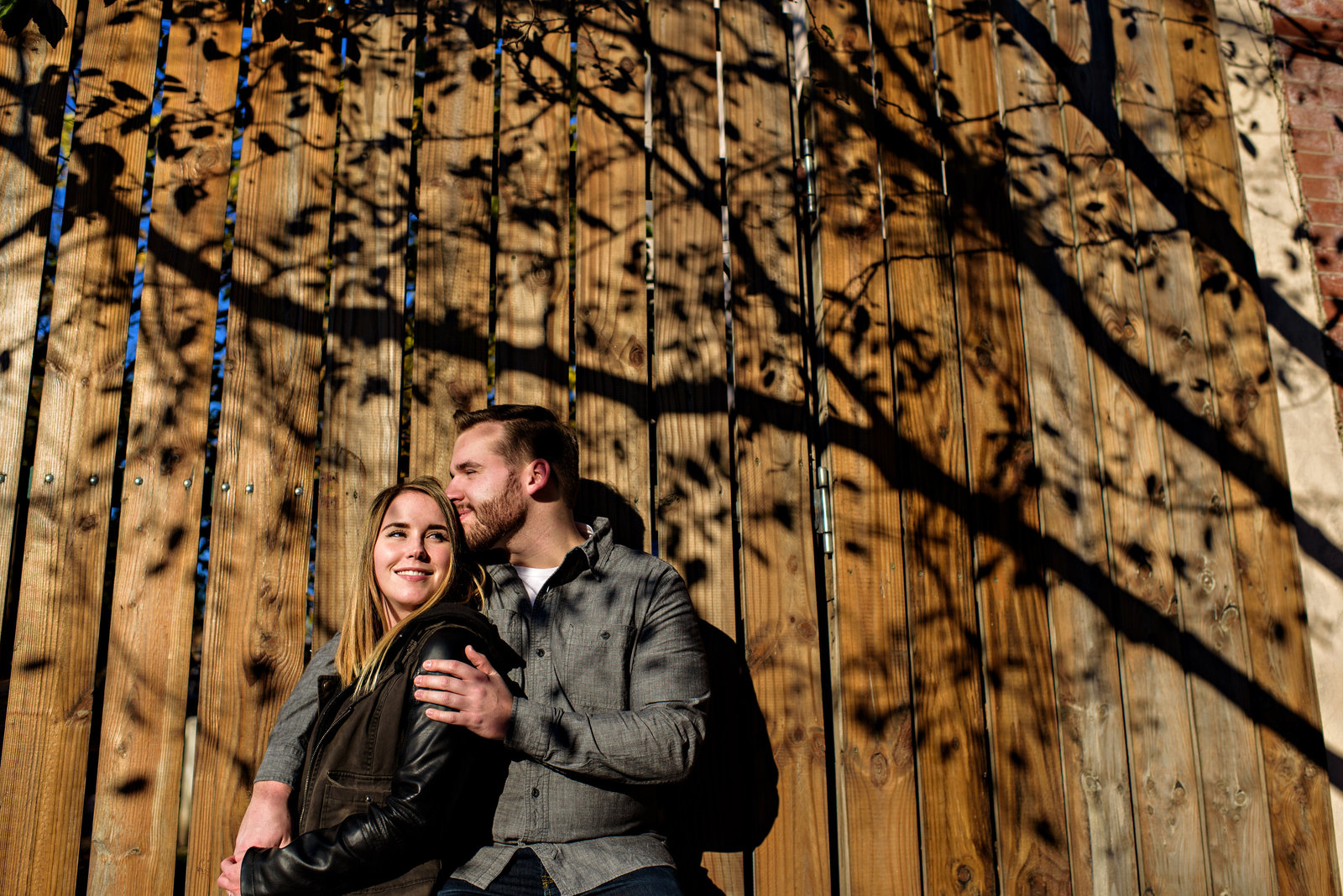 The shadow of a tree frame this fun couple in their engagement session.