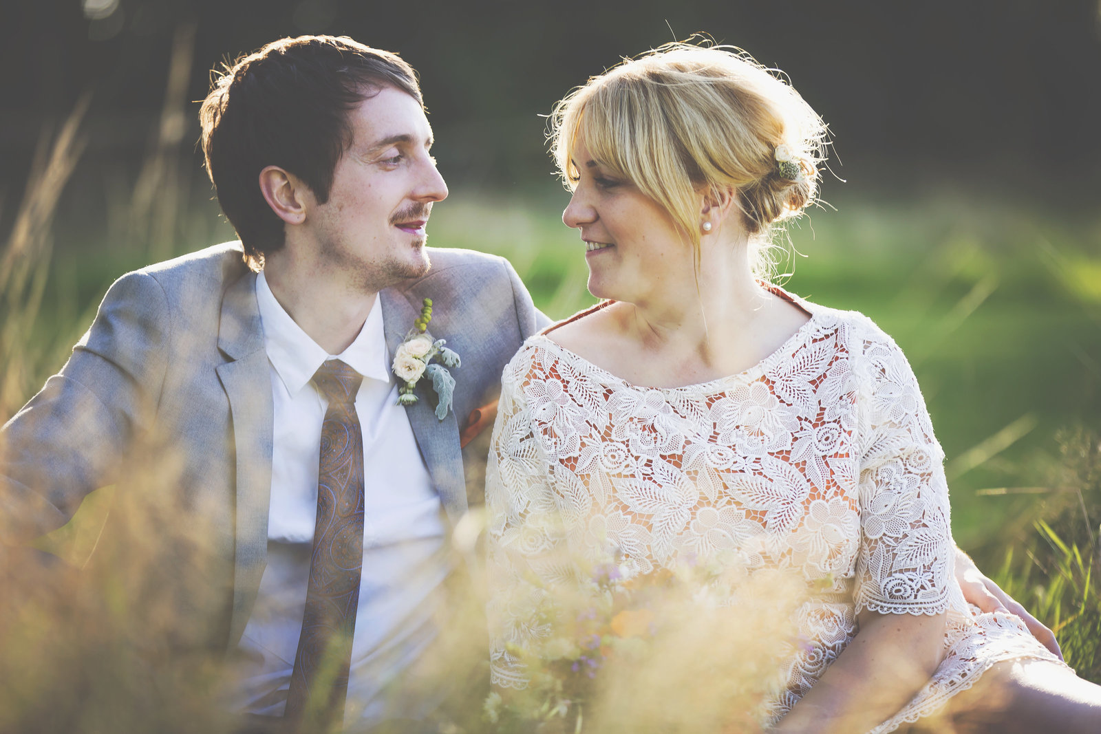Wedding at a campsite in Norfolk. Bride and groom sitting in the grass looking at each other