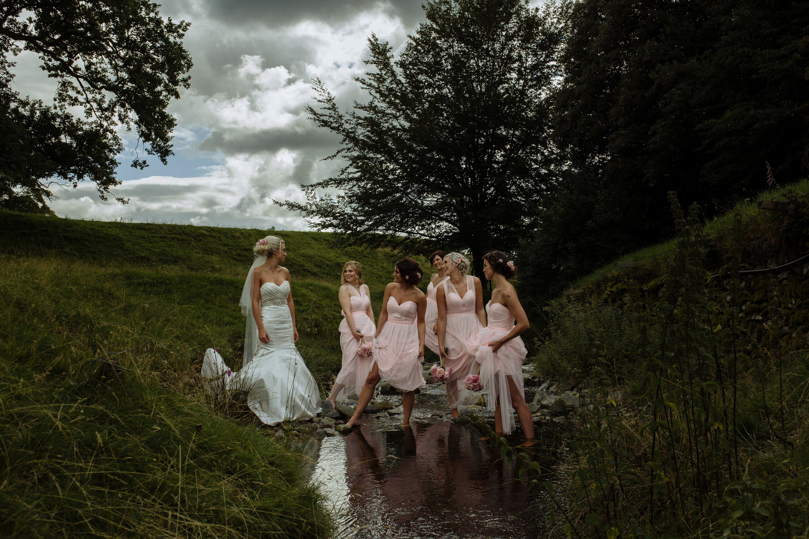Bridesmaids in stream in pink gowns. Whelprigg house photographer