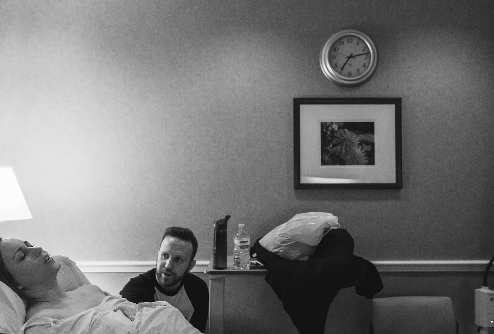 charlotte birth photographer jamie lucido captures documentary of laboring mother in hospital bed with father watching