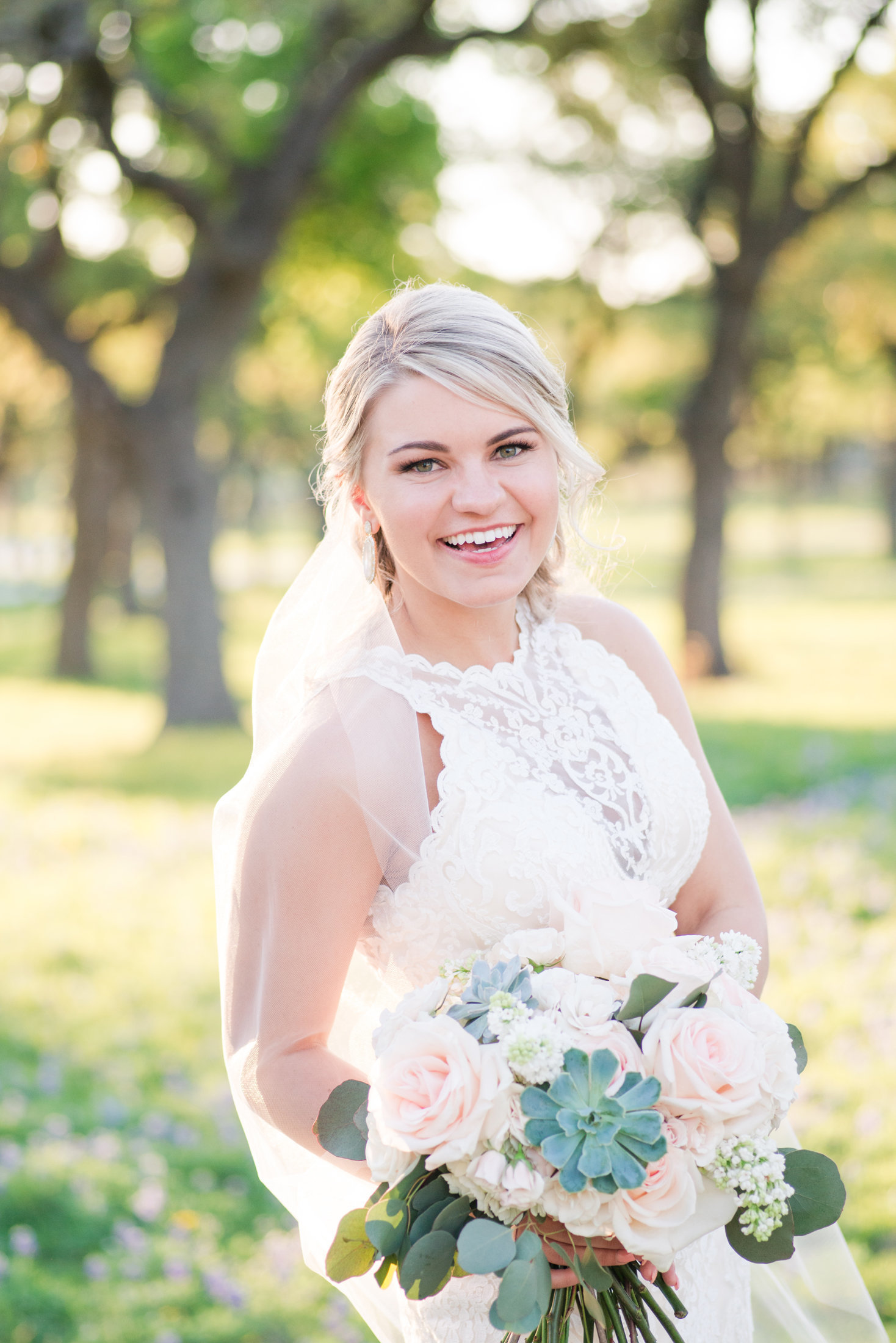 Bride in sottero and midgley wedding dress smiles with a blush rose and succulent wedding bouquet