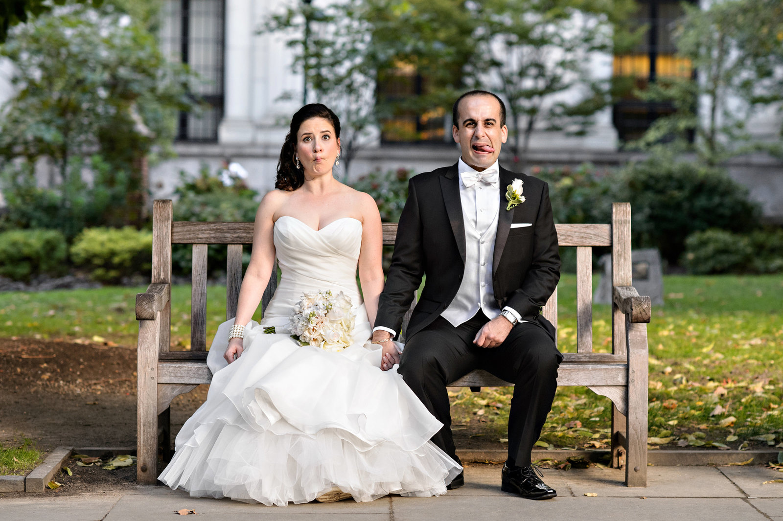 A wedding couple making funny faces in Washington Square Park in Philadelphia.