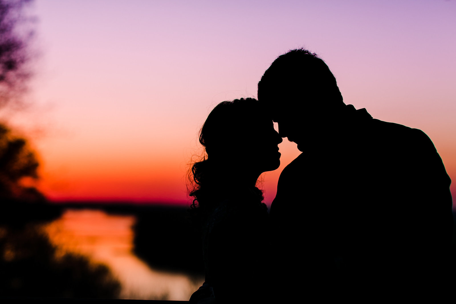 Bride and groom silhouette with the burning sunset in the background.