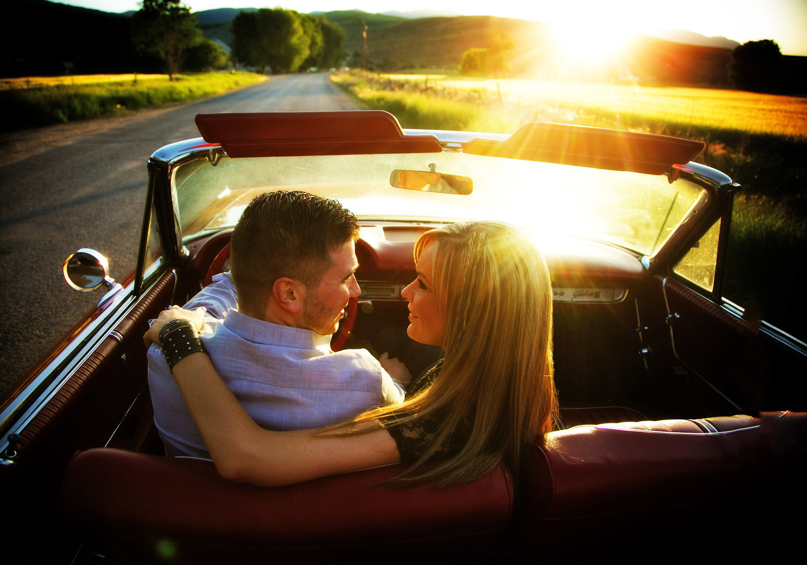 Engagement couple with car at sunset
