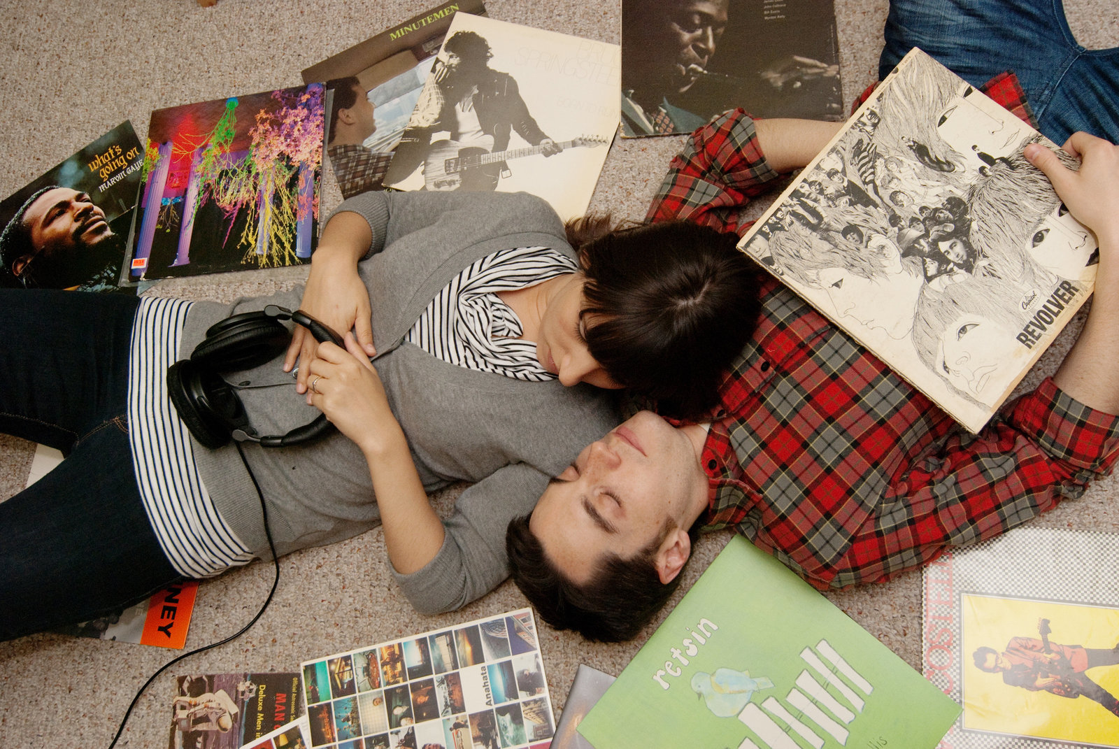 an engaged couple lay surrounded by vinyl records and headphones on their living room floor